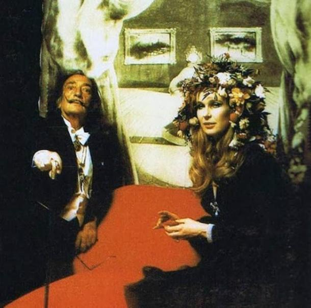 Salvador Dali doing his Dali face in front of his famous depiction of Mae West.