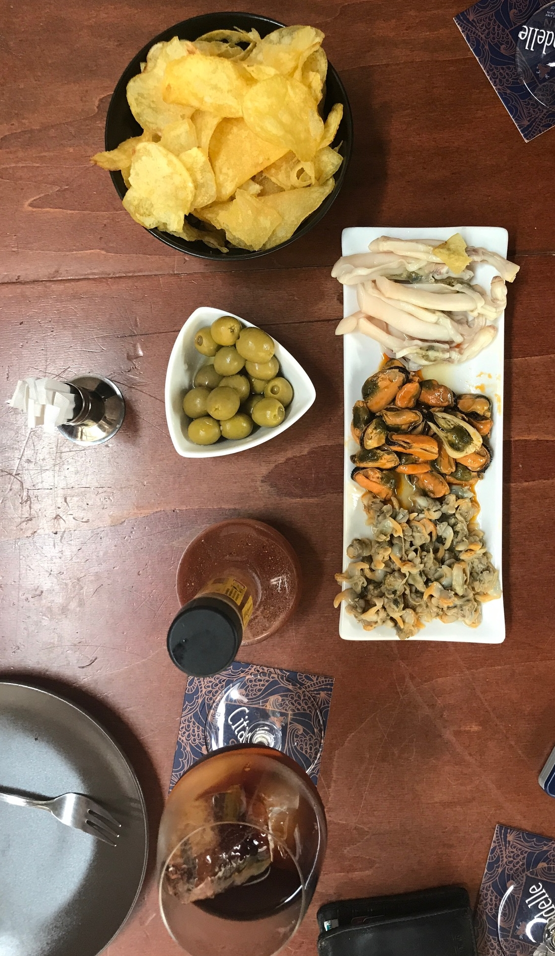 A simple pica-pica spread: selection of seafood conservas, olives, potato crisps and a refreshing vermouth