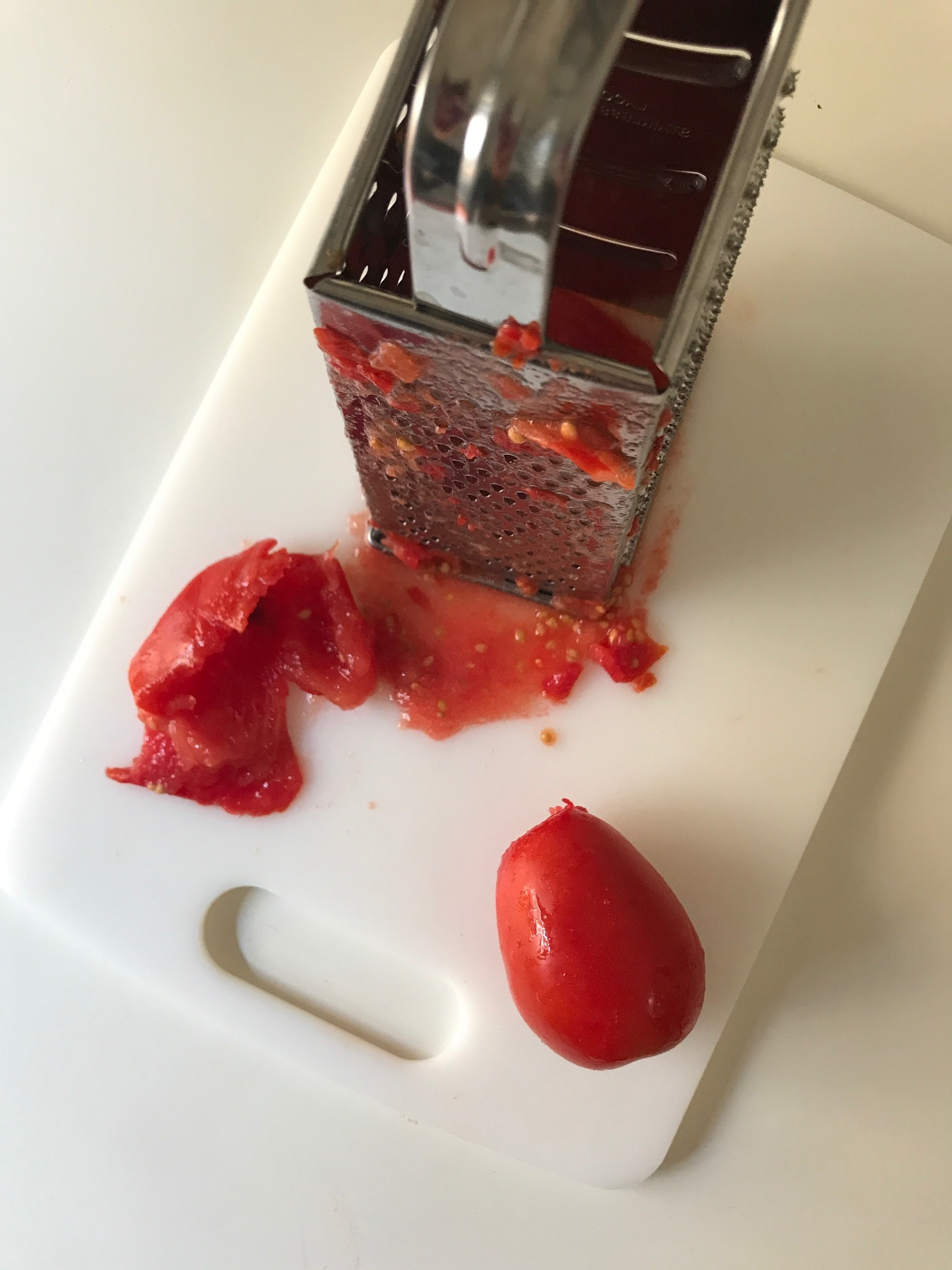 Grating tomatoes is an easy way to extract the pulp and juice leaving the skin behind.  Afterwards deseed by passing through a sieve