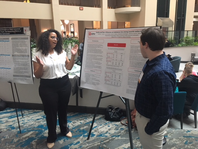 Richelle presents her poster to conference attendees