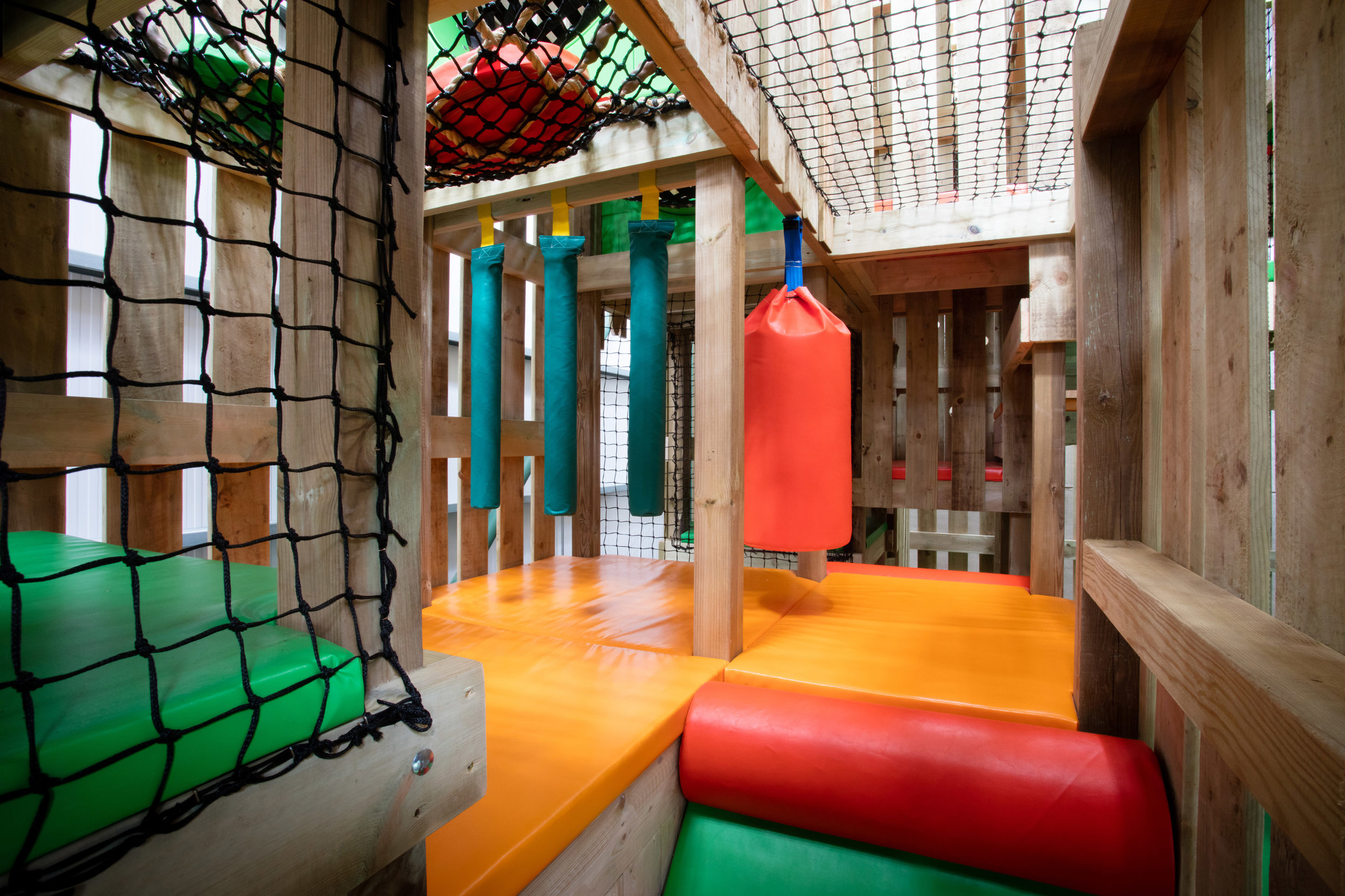 Hanging cylinders and punch bags offer obstacles as the little ones bound through the play area.