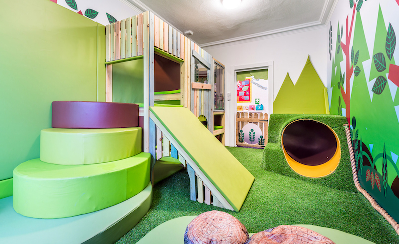 The timber play structure is surrounded by artificial lawn turf, offering a contemporary aesthetic.