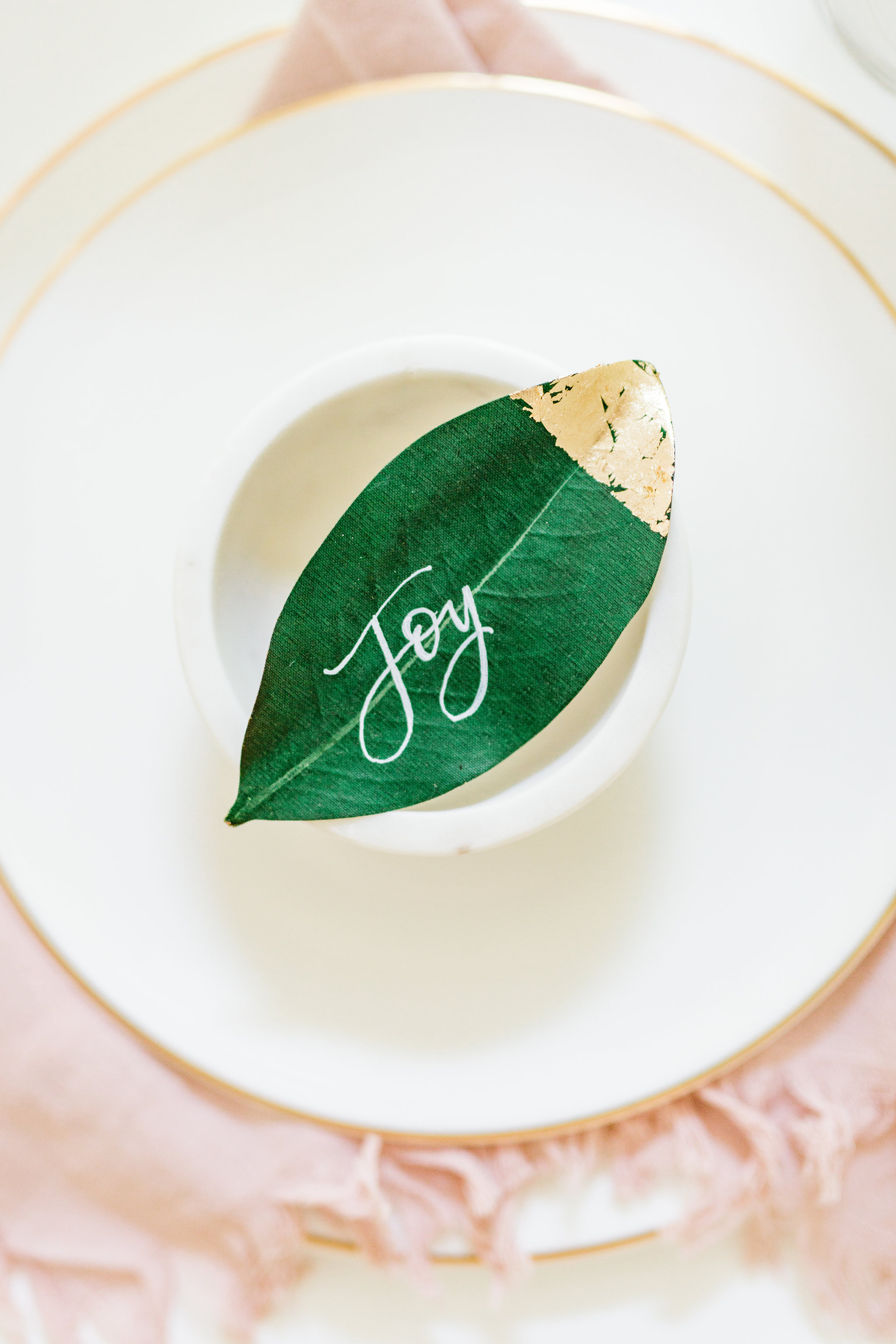 Olivia and Oliver Gold, Blush and Greenry Plants Gilded Garden Styled Bridal Shower Brunch with Bed Bath Beyond magnolia place setting chalk calligraphy Joyfullygreen.jpg