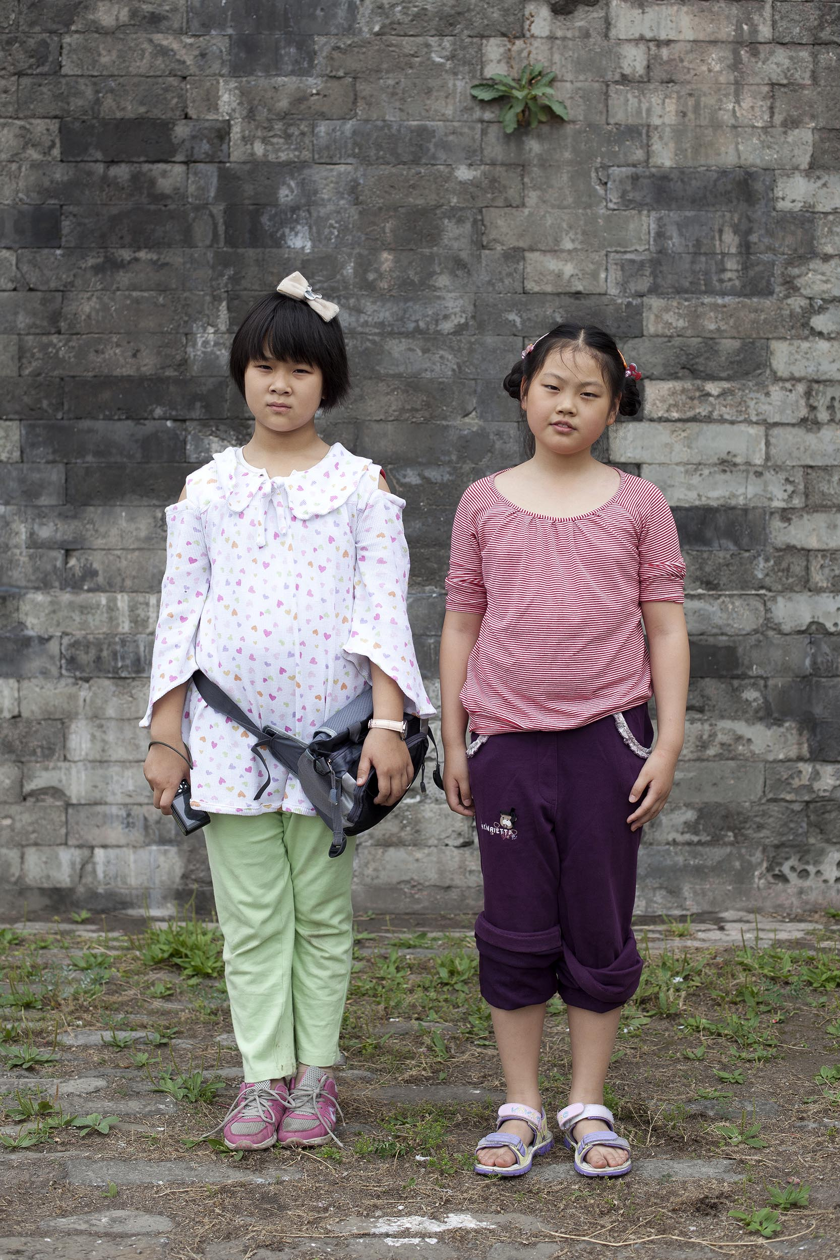 A portrait photograph of two young girls in the Forbidden City, Beijing , China  Documentary photography part of a personal project