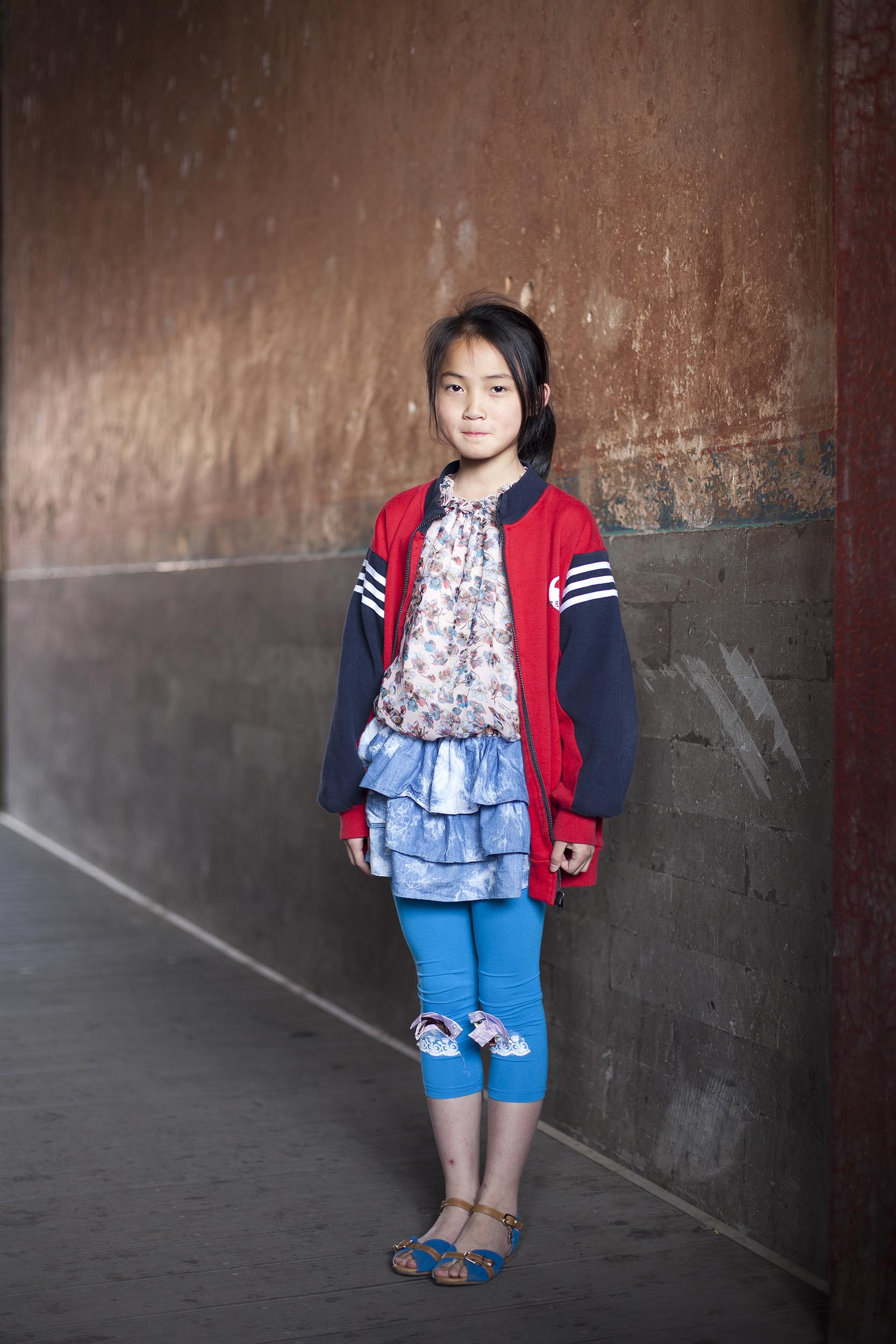 A portrait photograph of a young girl in the Forbidden City, Beijing , China  Documentary photography part of a personal project