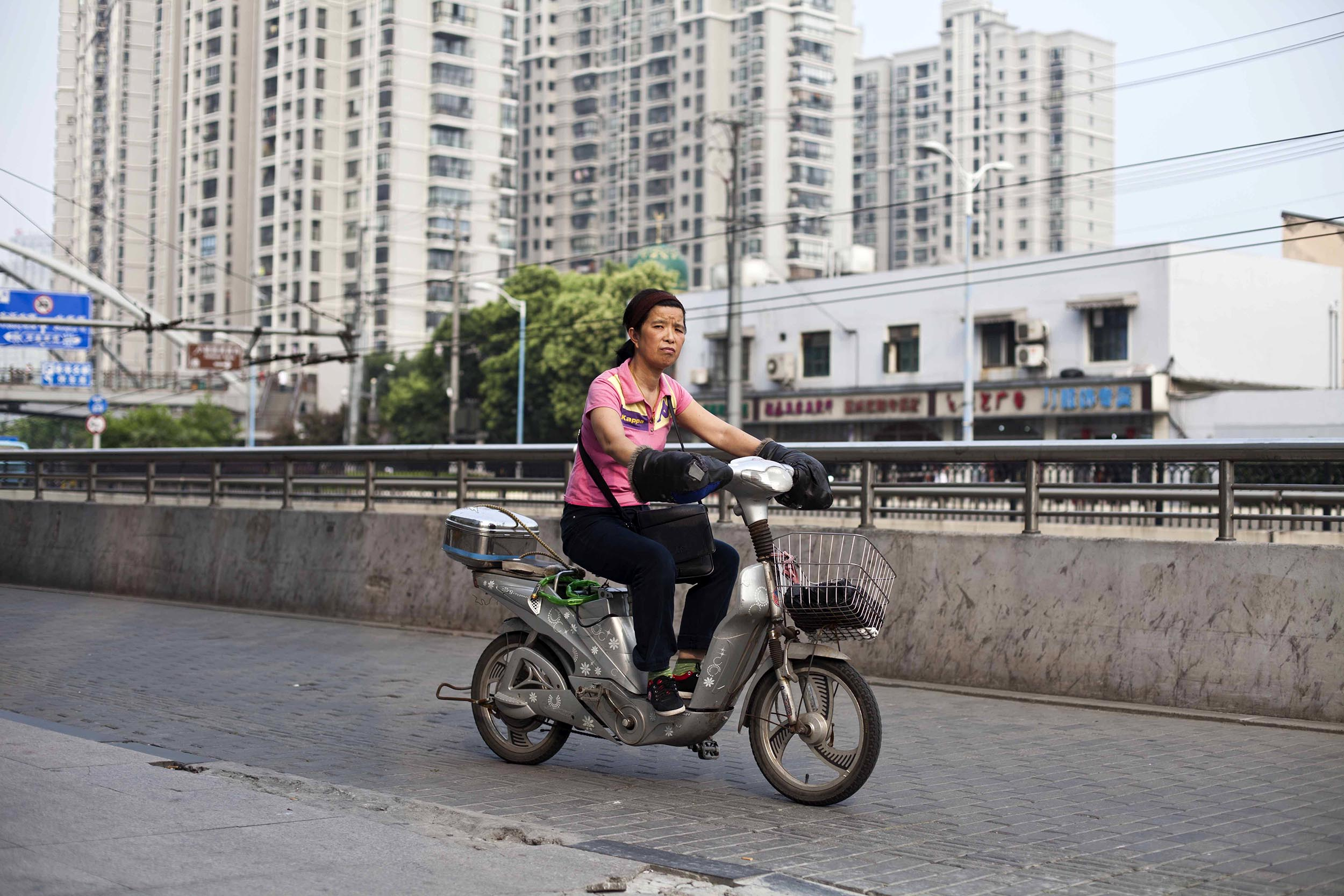 A photograph of woman riding a scooter in Shanghai, China  Photography for personal project