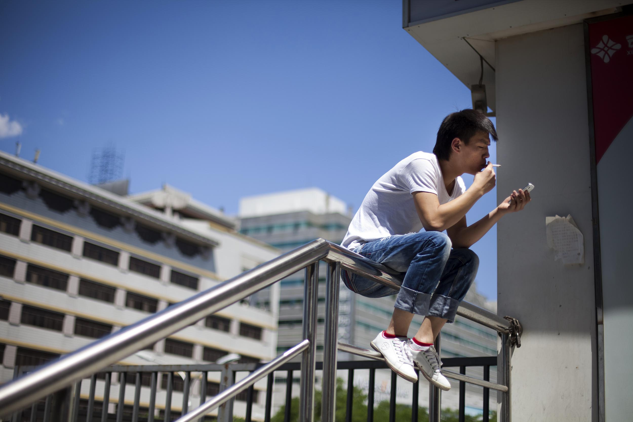 A photograph of a young man smoking in Beijing, China  Photography for Beijing Government