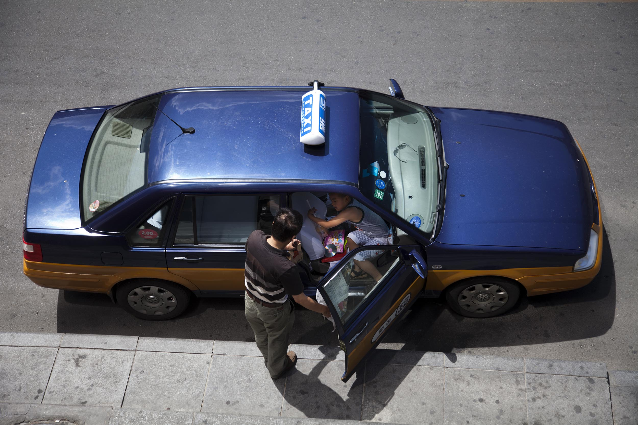 A photograph of people entering a taxi in Beijing, China  Photography for Beijing Government