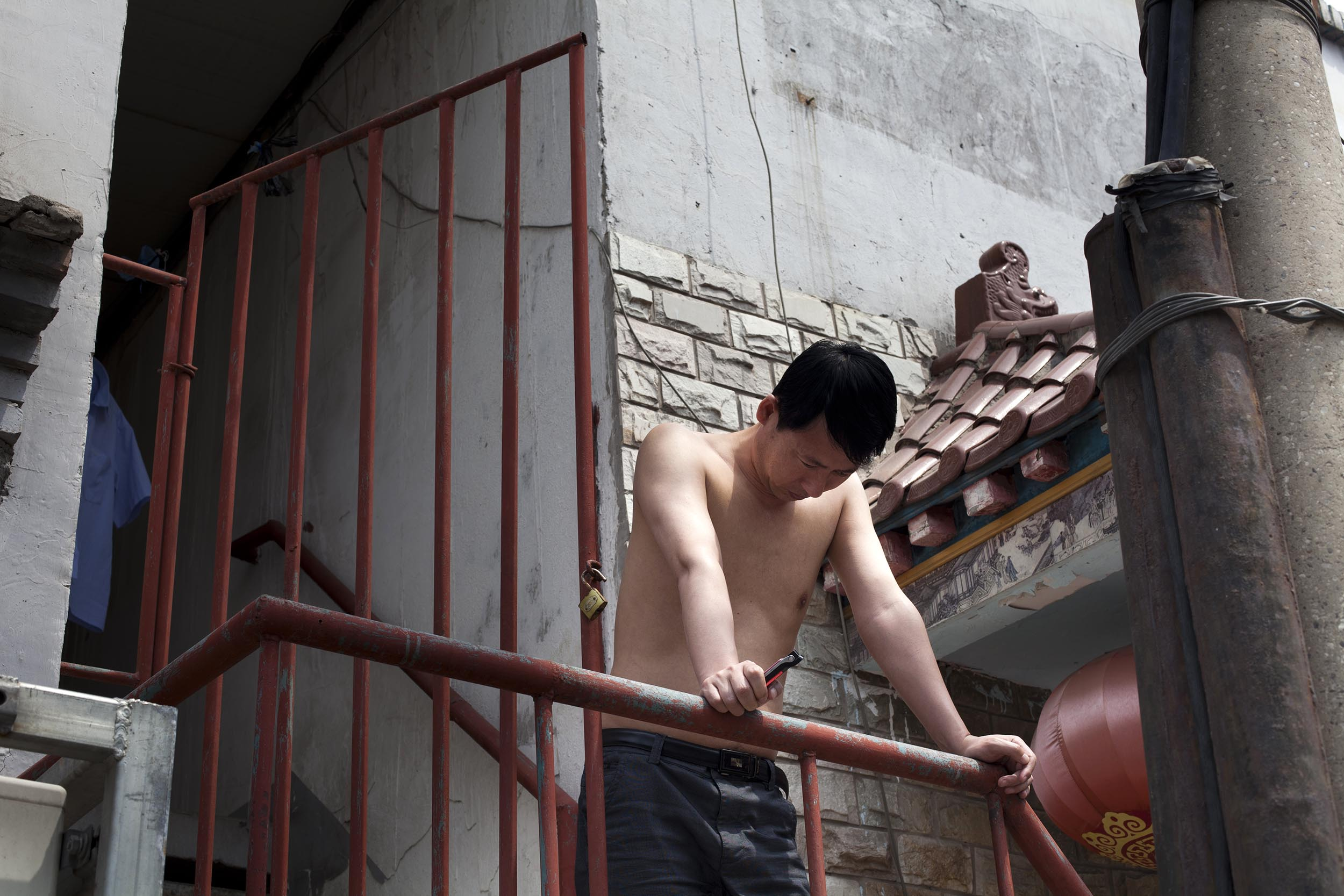 A photograph of a young man on balcony in Beijing, China  Photography for Beijing Government