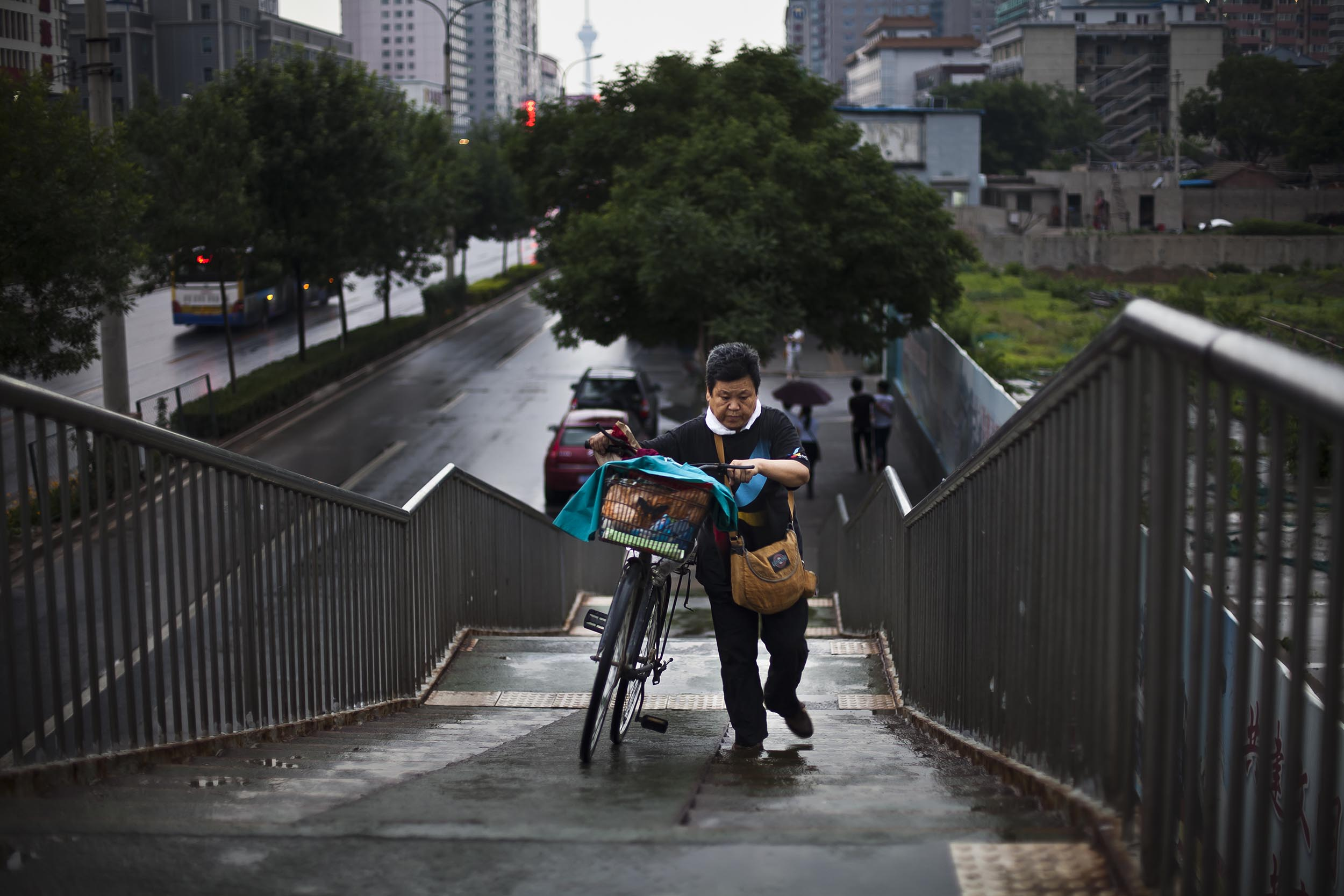 A photograph of a woman pushing bicycle up stairs in Beijing, China  Photography for Beijing Government