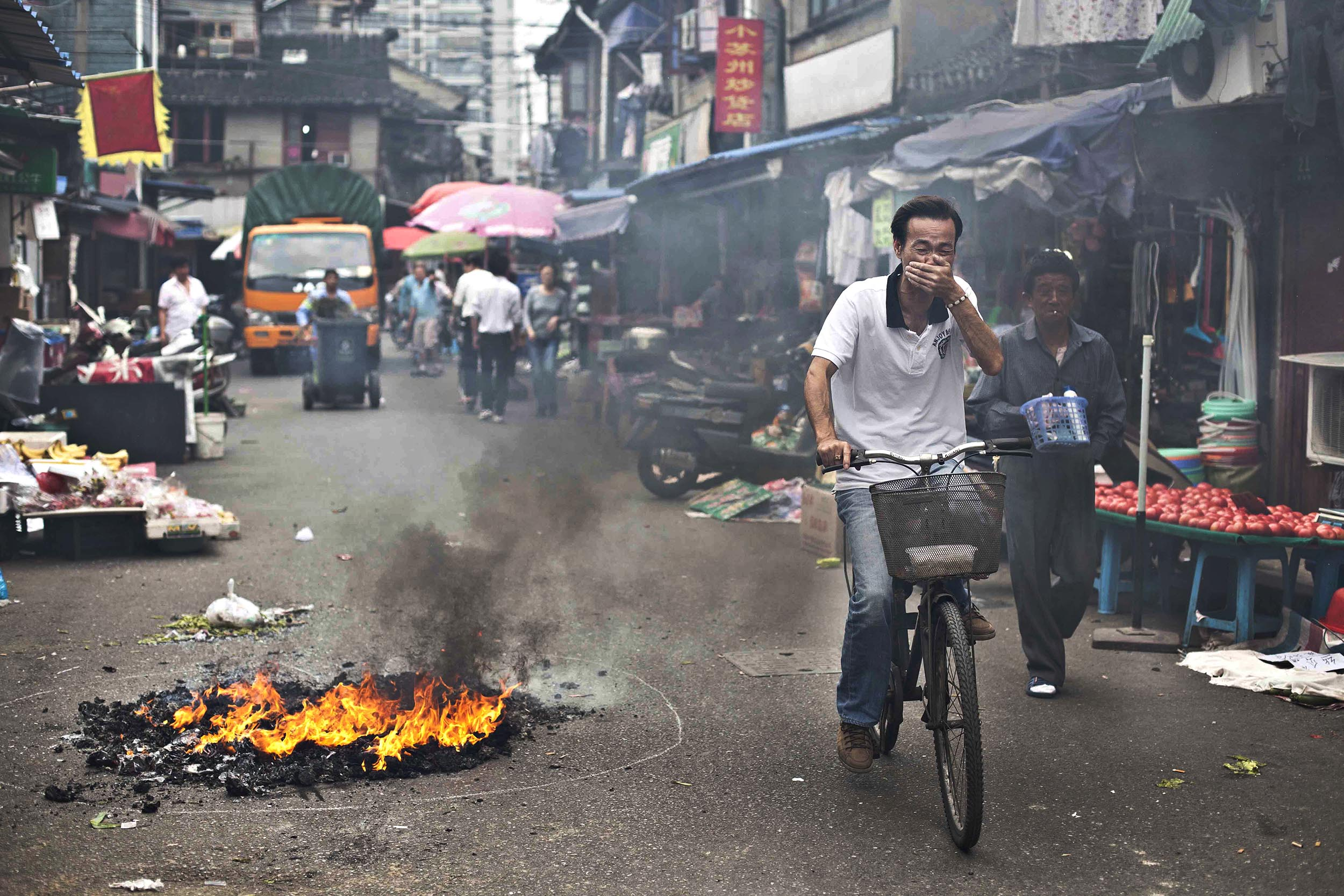 A photograph of cycling past burning rubbish in Shanghai, China  Photography for personal project