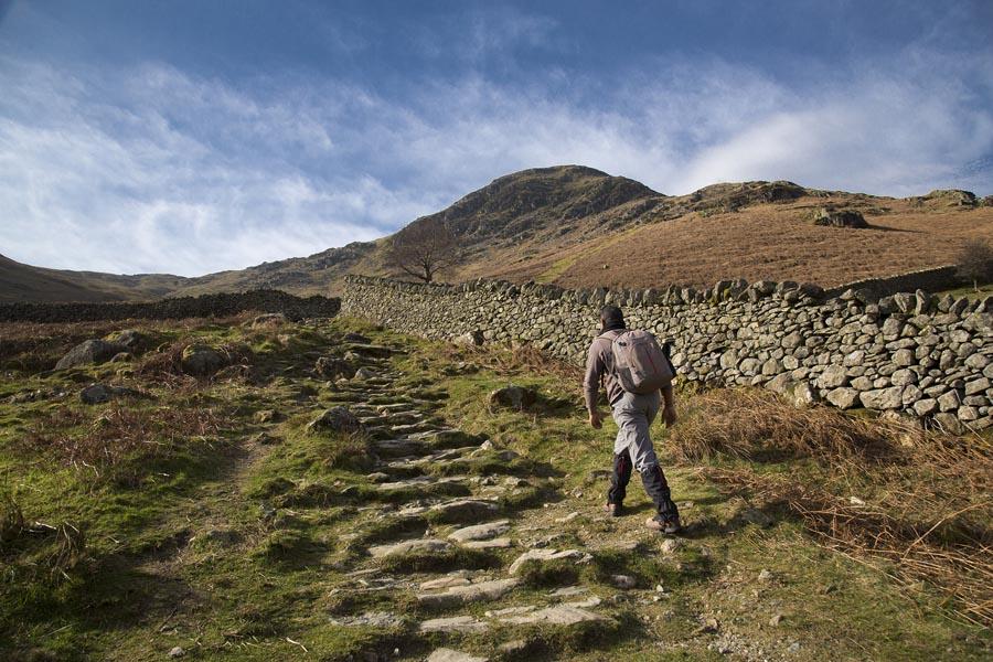 A photograph of a hiker ascending Helvellyn, Lake District, Cumbria, England