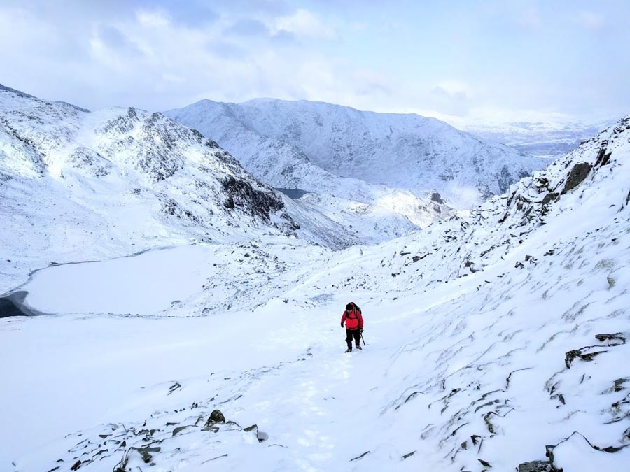A photograph of a hiker ascending Old man of Coniston, Lake District, Cumbria, England