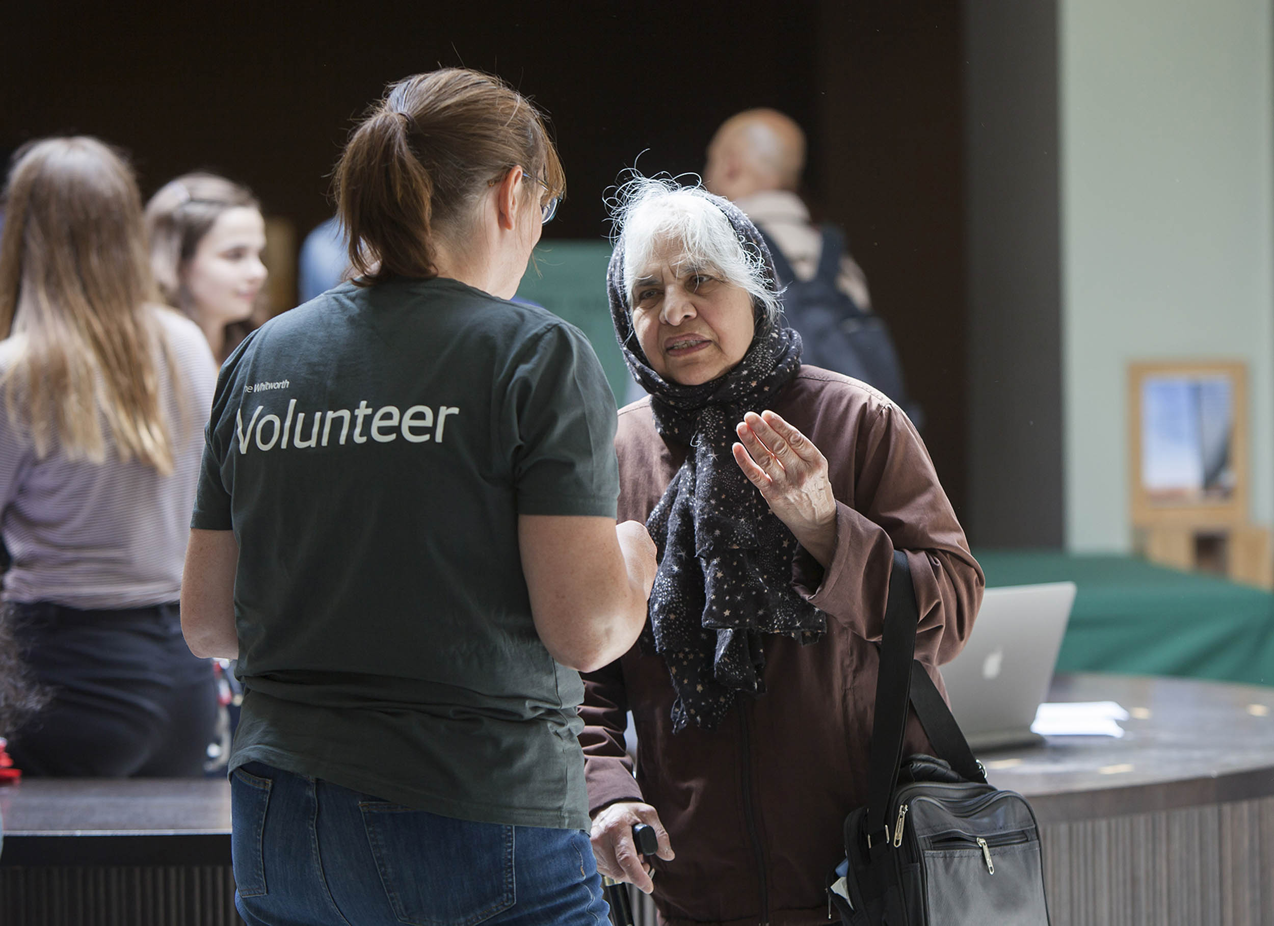 A documentary photograph of the a volunteer speaking to a visitor at an event.  Photography commissioned by Whitworth Art Gallery, Manchester