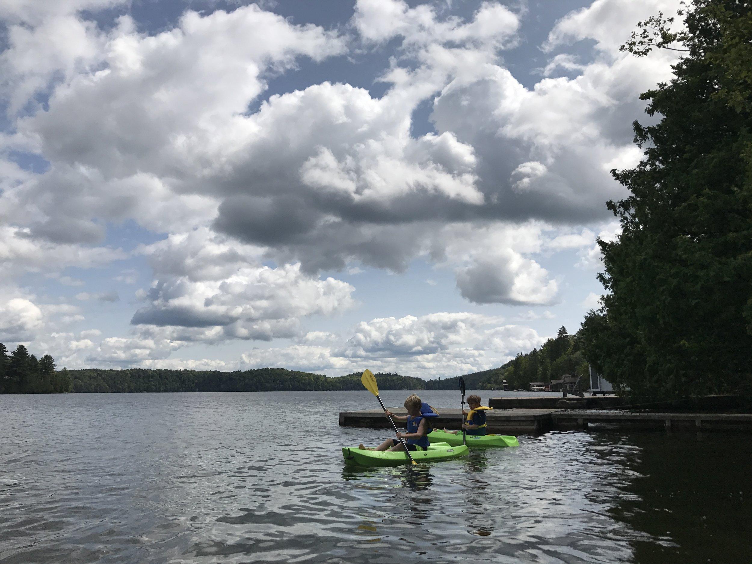 Kayaking buddies paddling Meech Lake.