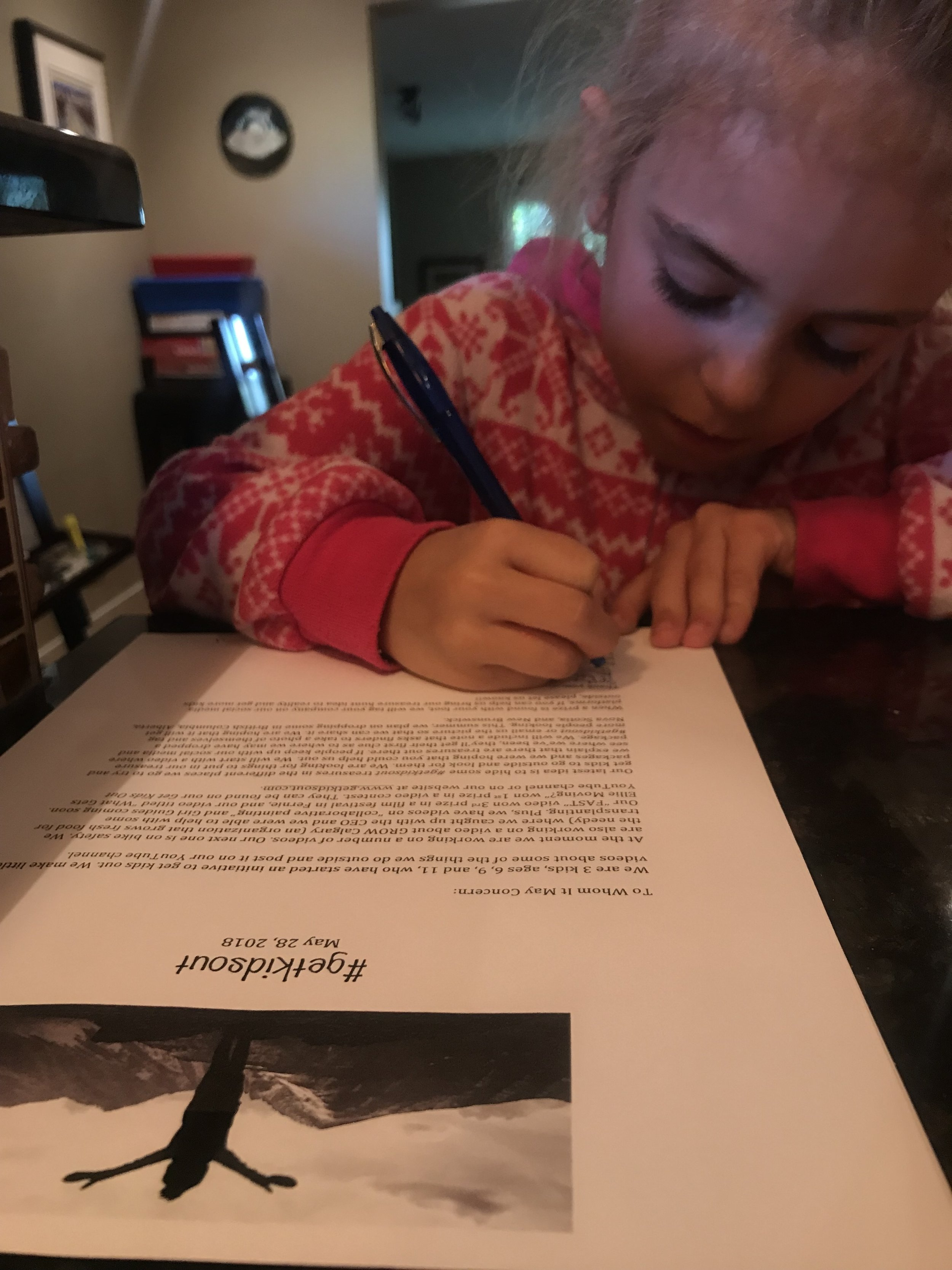 Ellie signs letters for businesses.