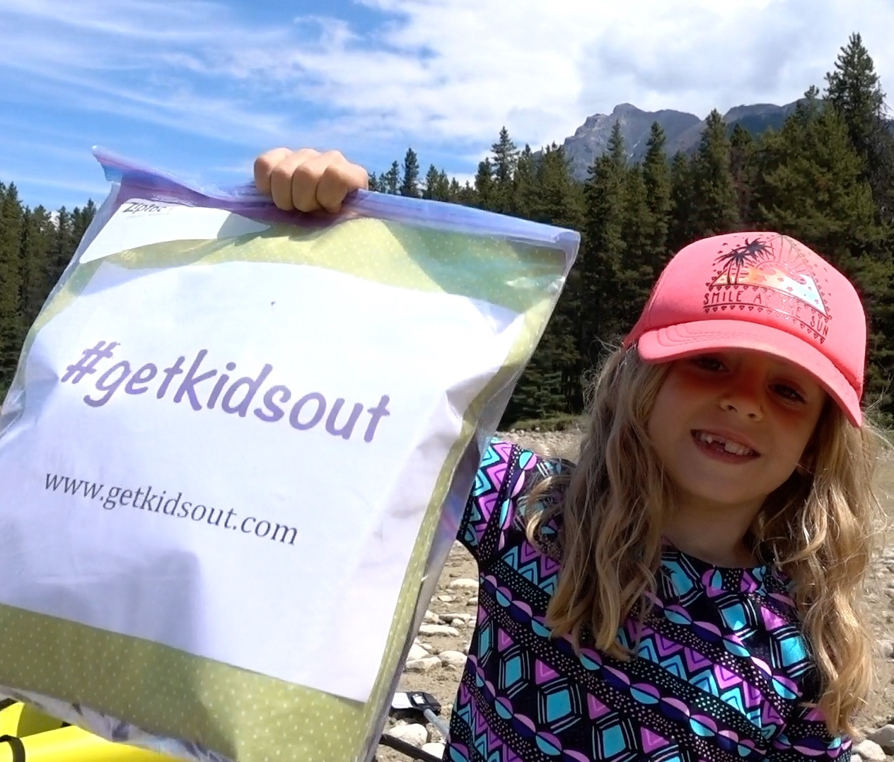 Ellie holds up a #getkidsout bag on launch day.