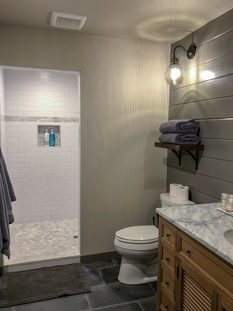 The custom shower has two shower heads - a rain shower and adjustable shower head