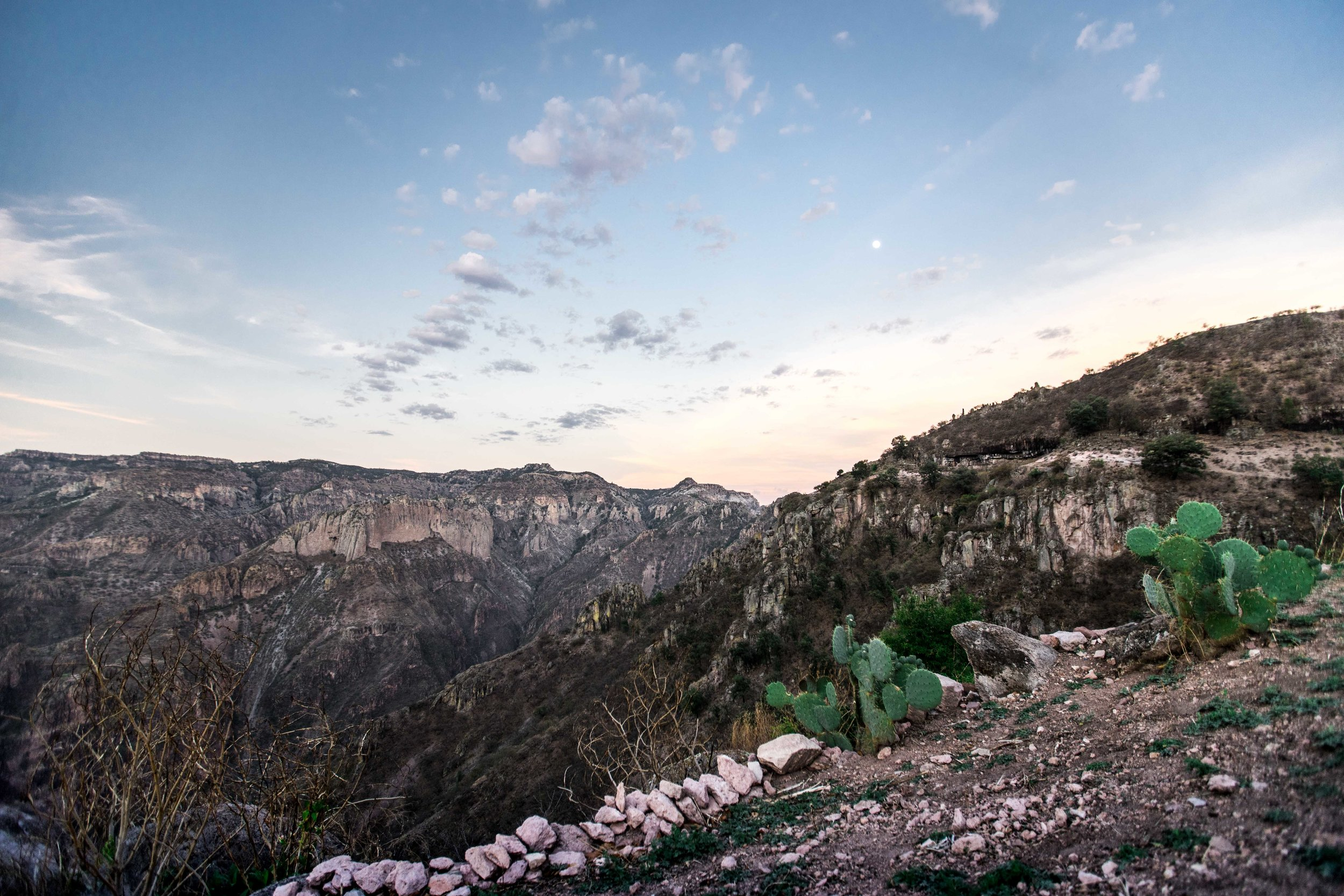 BARRANCAS DEL COBRE - INNER STRENGTH AND SOLITUDE // A SENSE OF SPACE AND TIMEOur journey into the Barrancas del Cobre, Mexico's northernmost Copper Canyons, is an epic adventure into one of the world's last true wildernesses. We will venture deep into the canyons' inner sanctum, trekking up sheer mountain trails and camping under the open stars by firelight. This voyage will challenge your body, mind, and spirit, and we will carry all we need on our backs as we trace our steps away from civilization into the silent echoes of these vast and desolate ranges. Every evening, our group will congregate around the campfire and co-create space for inner contemplation and connecting back to the wonders of the wild.This journey features:- Two nights in charming rustic hotels in Creel and Divisadero and two nights camping under the stars around campfires.- Three days trekking precipitous mountain trails and ascending exhilarating peaks with a local guide, bathing in hidden waterfalls and meandering through the magnificent Valle de los Monjes.- An introduction to local NGO Tierra Nativa and their work with the nomadic Tarahumara tribe.- Our founders' participation and orchestration of adventures.
