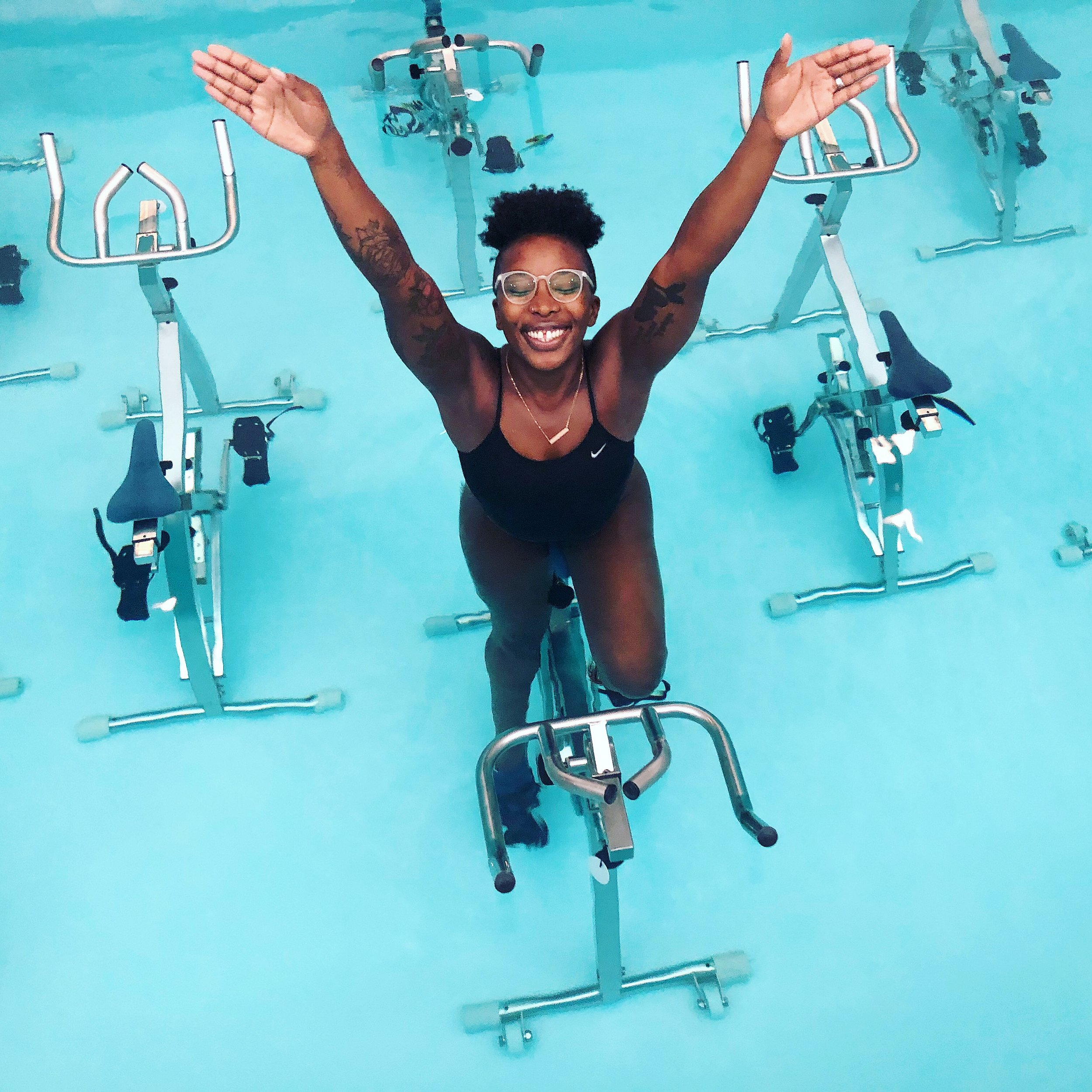 """Alvina Brown - Born and raised in the athletic world, Alvina has always gravitated towards adrenaline workouts and activities. While Alvina is full of energy and joy, as a NASM certified personal trainer and certified Yoga Teacher, she also appreciates the science behind exercising and the benefits of a well-rounded yoga practice. After taking her first FLOW AQUA Class, she was drawn to the yogi aspects of this relaxing yet challenging class and fell in love with the format. Alvina's philosophy is: """"numbers do not matter; feeling good and eating good food is when the magic happens"""". When she is not teaching, Alvina enjoys traveling the world and immersing herself in each culture but also relaxing and detaching from her phone. Be prepared for a knowledge-filled and challenging workout to further your fitness journey.Her Favorite Class: FLOW"""