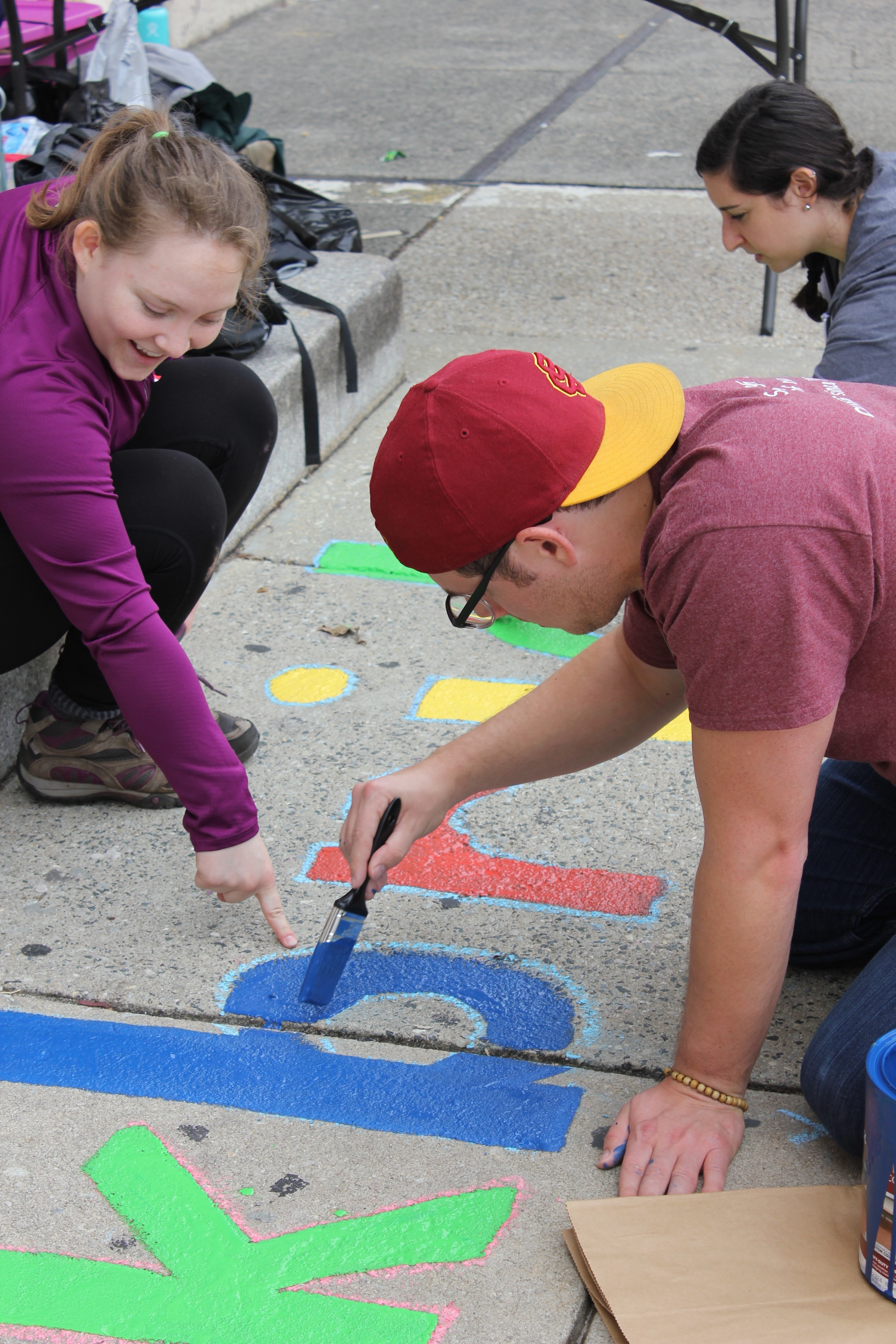 Two of our volunteers work to paint our partner school's name on the pavement