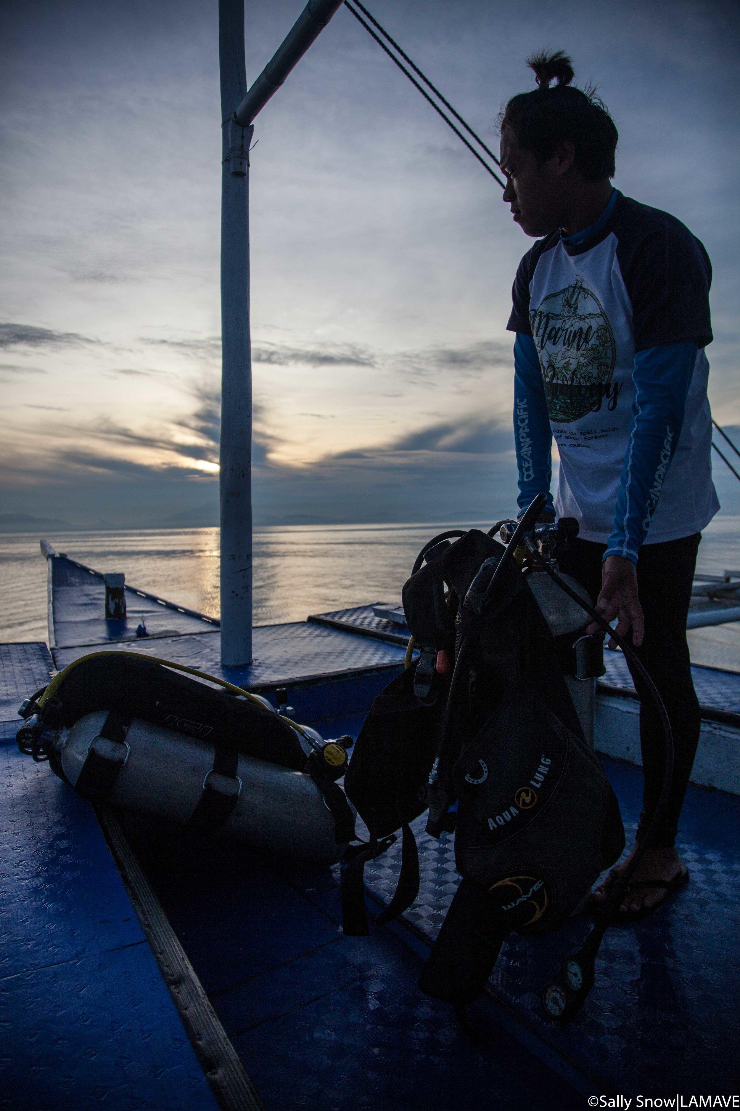 Jemar prepares his scuba gear as the sun rises over the volcanic horizon of the Bicol Region.