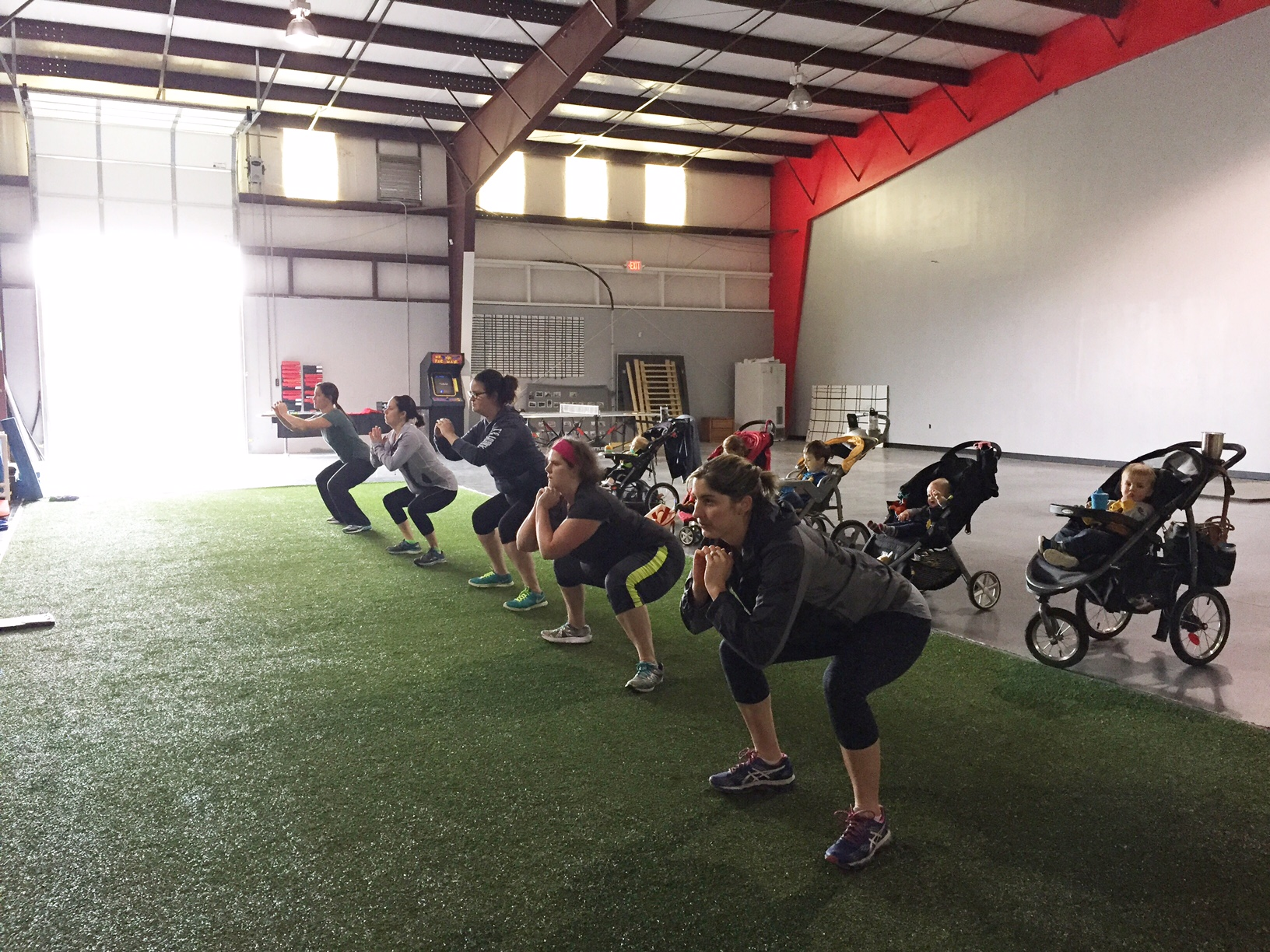 Moms doing bodyweight squats in a fitness class