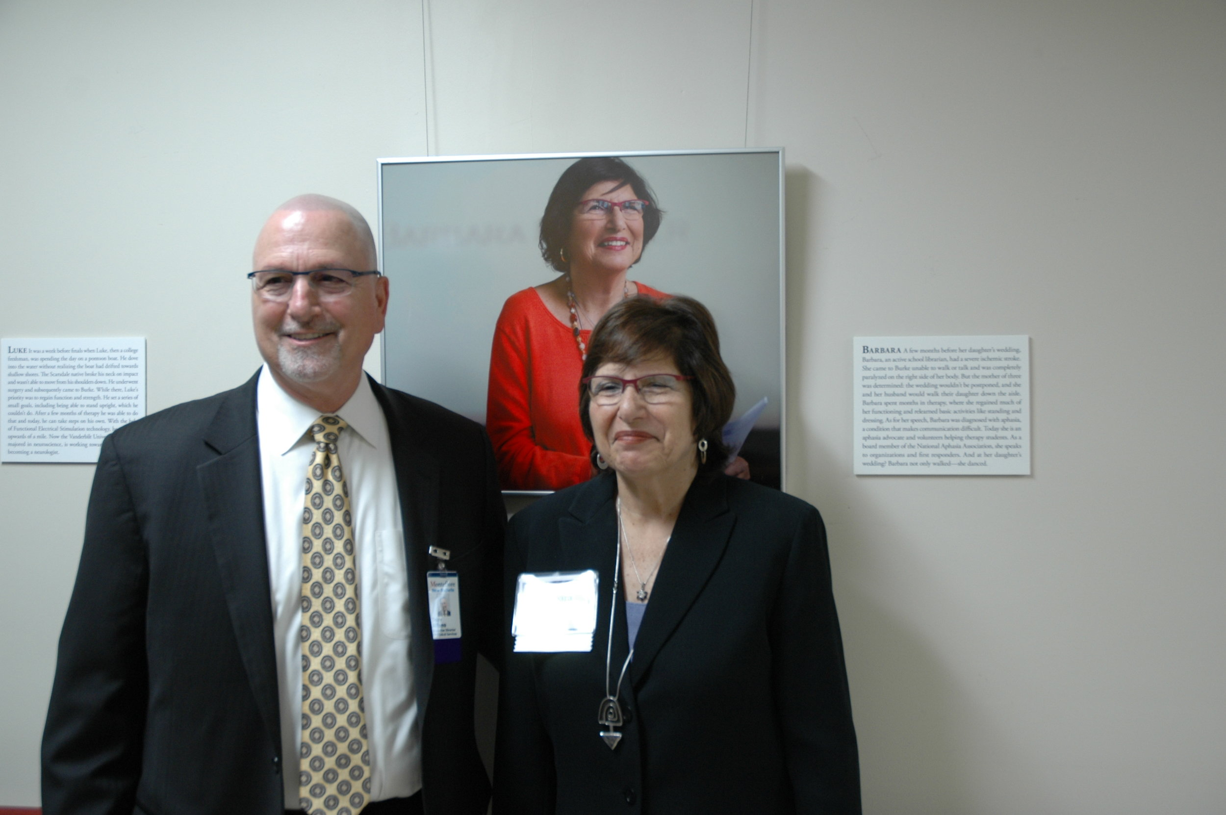 Anthony Alfano (left), Vice President and Executive Director at Montefiore New Rochelle, standing with Barbara (right), Faces of Burke participant, in front of her portrait