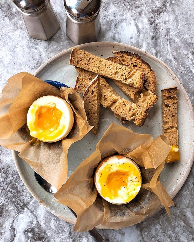 "Eggs with Soldiers || This has become my new favorite breakfast! Something about soft-boiled eggs 🤤🤤🤤. @cocobakes #glutenfree sourdough ""soldiers"" with two soft-boiled @vitalfarms eggs (HOW TO: bring water to a boil, cook eggs for 6.5 mins. Remove from water and place in ice bath. Peel top half of egg and place in egg cups or parchment-lined espresso cups. Remove upper whites and dip bread into runny yolks) . . . #thehealthmason #softboiledegg #glutenfree #glutenfreebreakfast #cocobakes #saturdaymorning #saturdaybrunch #baltimoreblogger #healthyfoodporn #yolkporn"