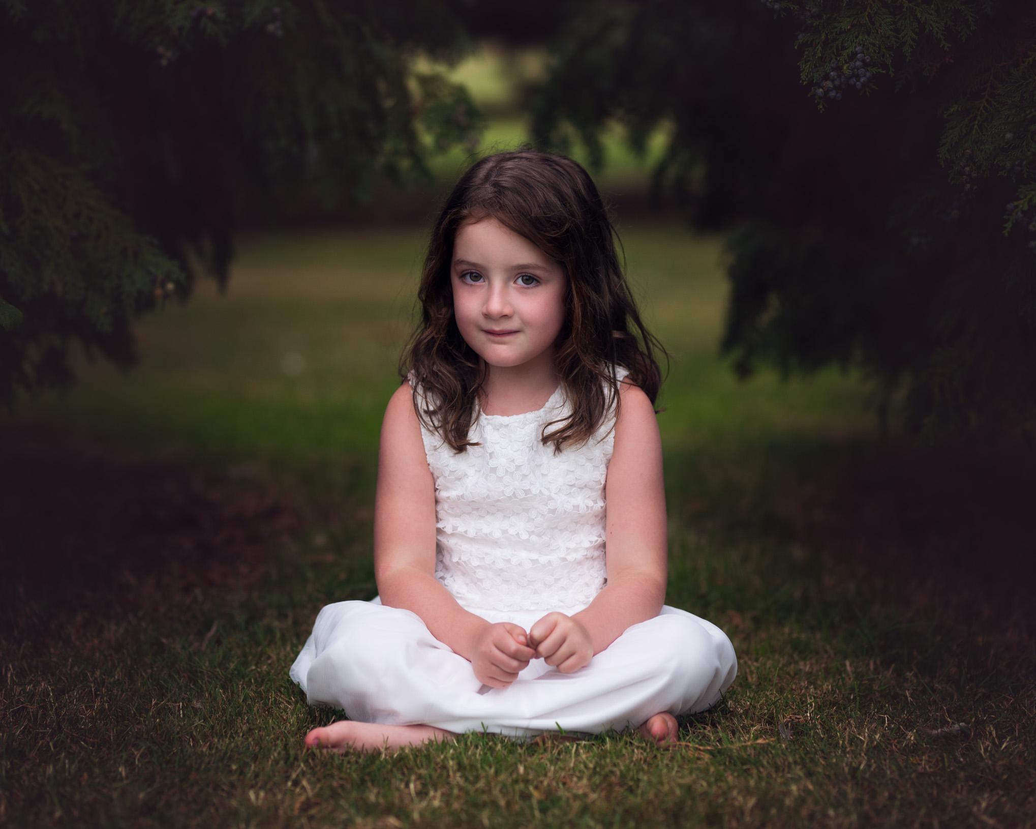 Girl sitting between trees | Children's Photography