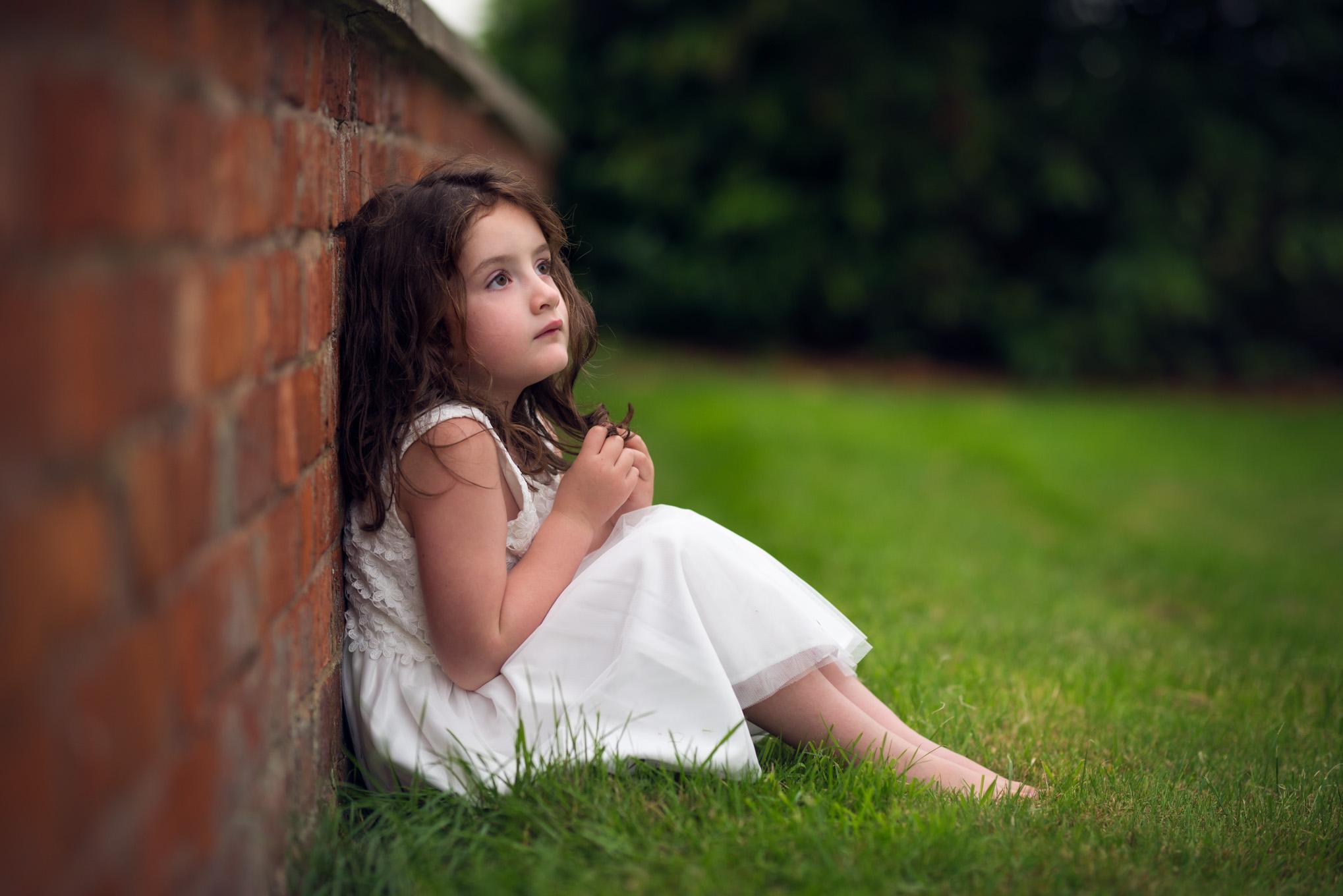 Girl in white dress sat against wall | Children's Photography