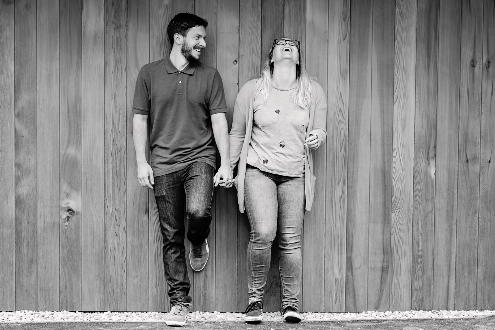Holding hands laughing against a wooden wall - Cotswolds Wedding Photographer