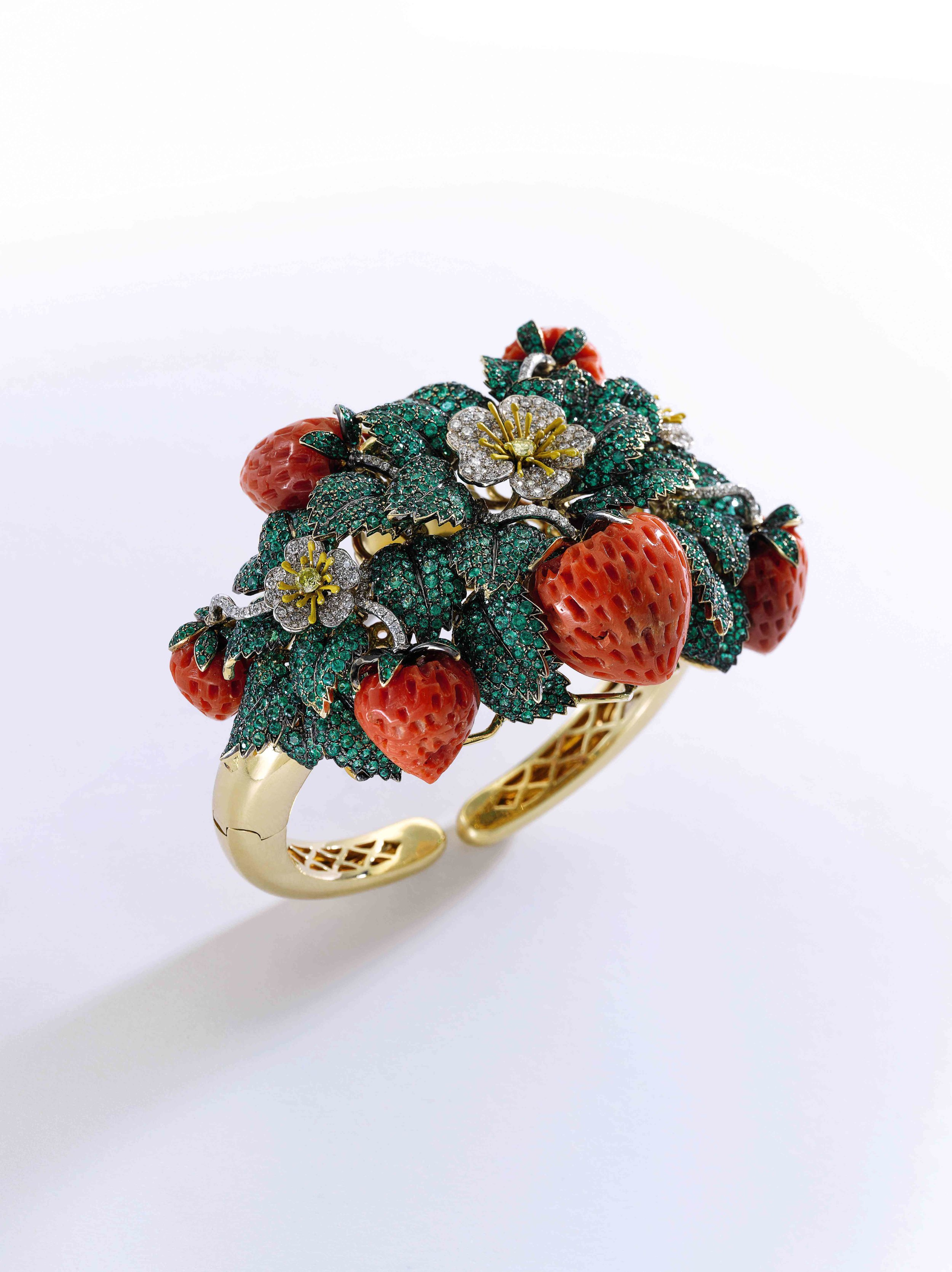 Coral, emerald, enamel and diamond bangle, 'Fragole' Of strawberry design, the fruits carved in coral, the leaves pavé-set with emeralds, the flowers and stems set with diamonds
