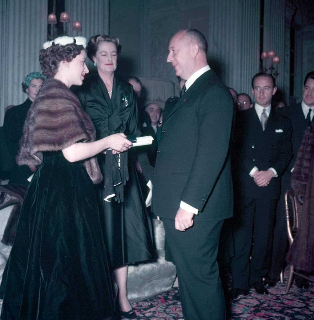 Princess Margaret (left), with the Duchess of Marlborough behind, presents Christian Dior with a scroll entitling him to Honorary Life Membership of the British Red Cross after the presentation of his Winter Collection at Blenheim Palace on 3rd November 1954  © Popperfoto / Getty Images