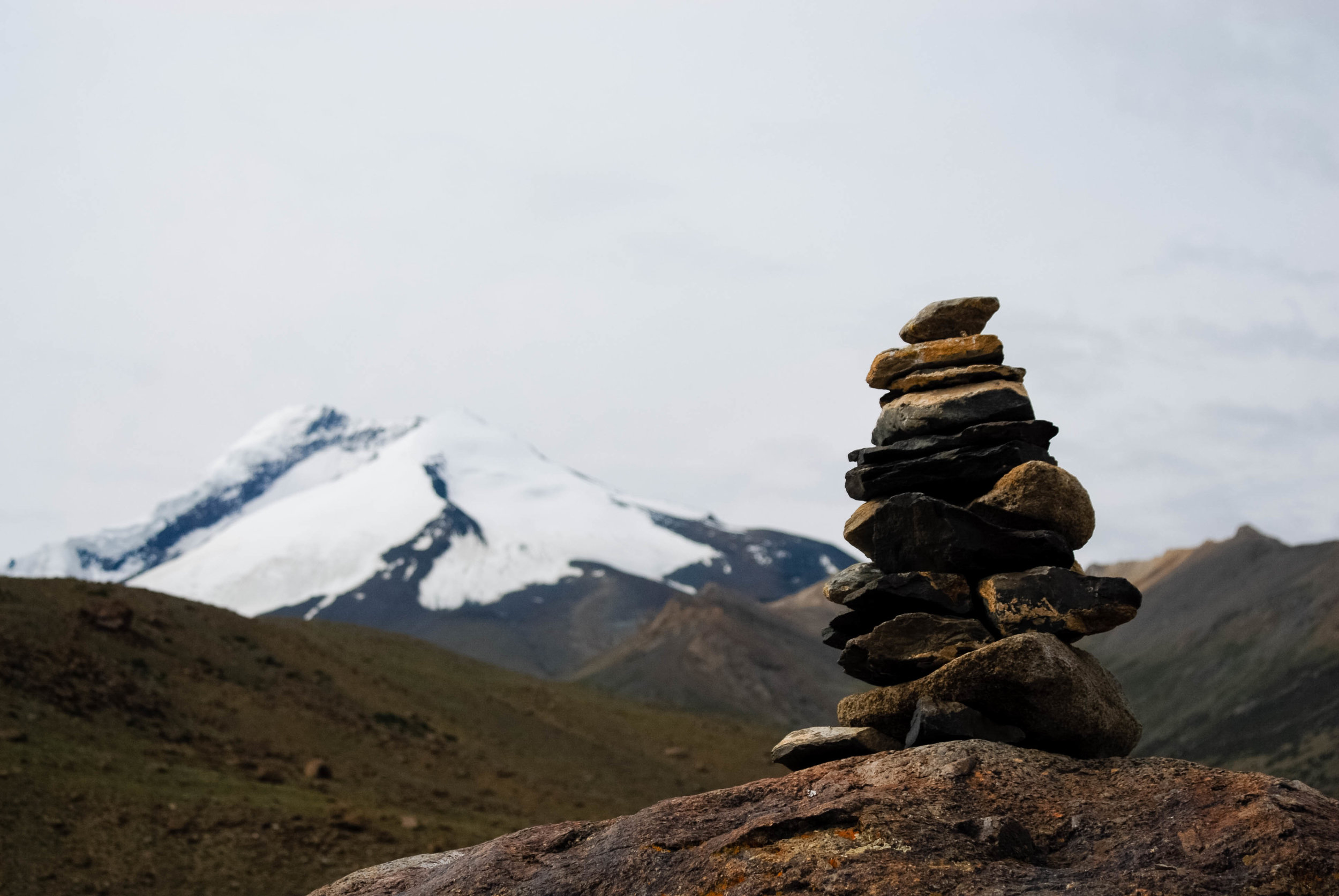 A stone cairn with the Kang Yaze peak behind it.