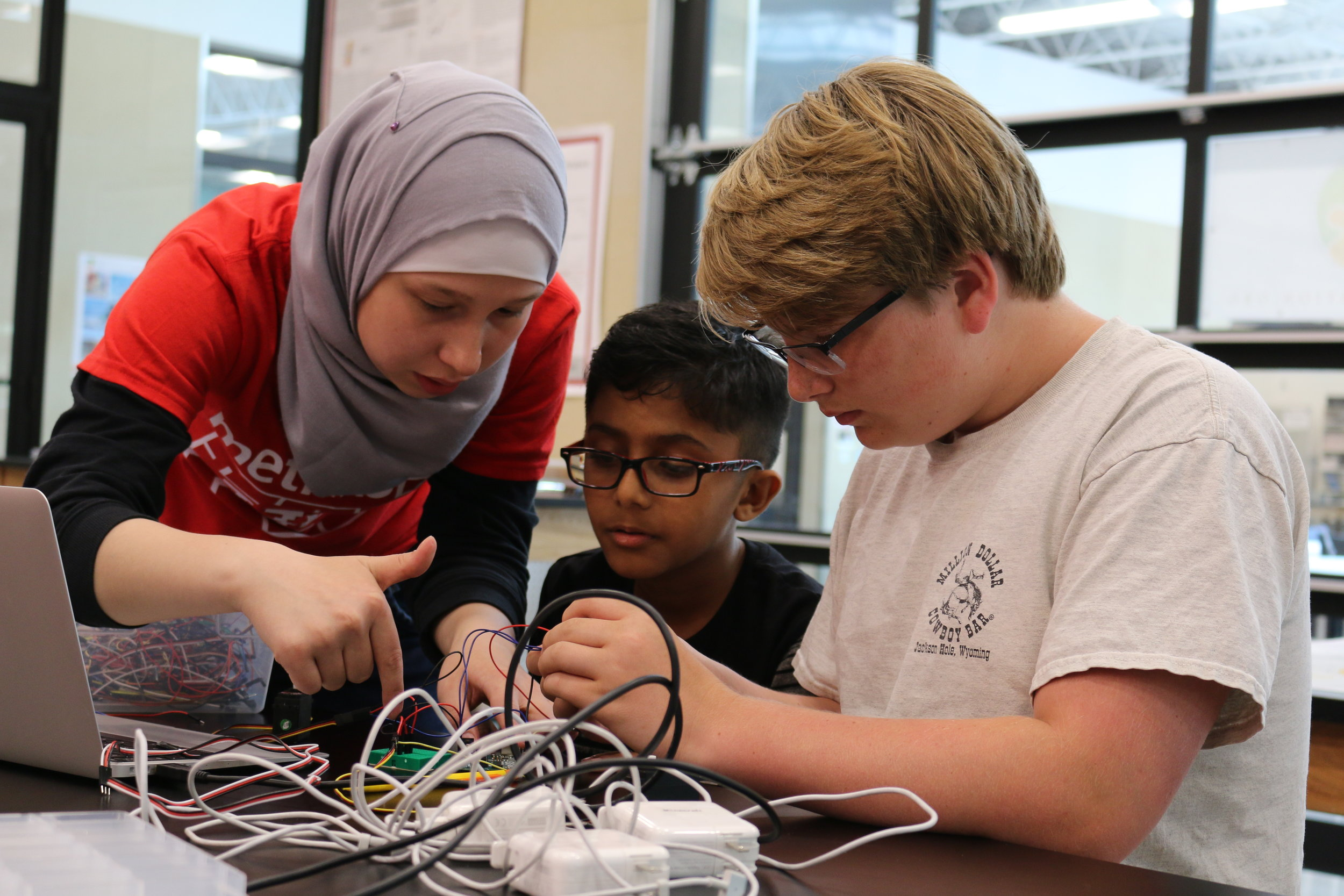 Intermediate Robotics Summer Camp(Summer 2018)-A senior on the team, Fatima(left) volunteers to help students learn how to breadboard