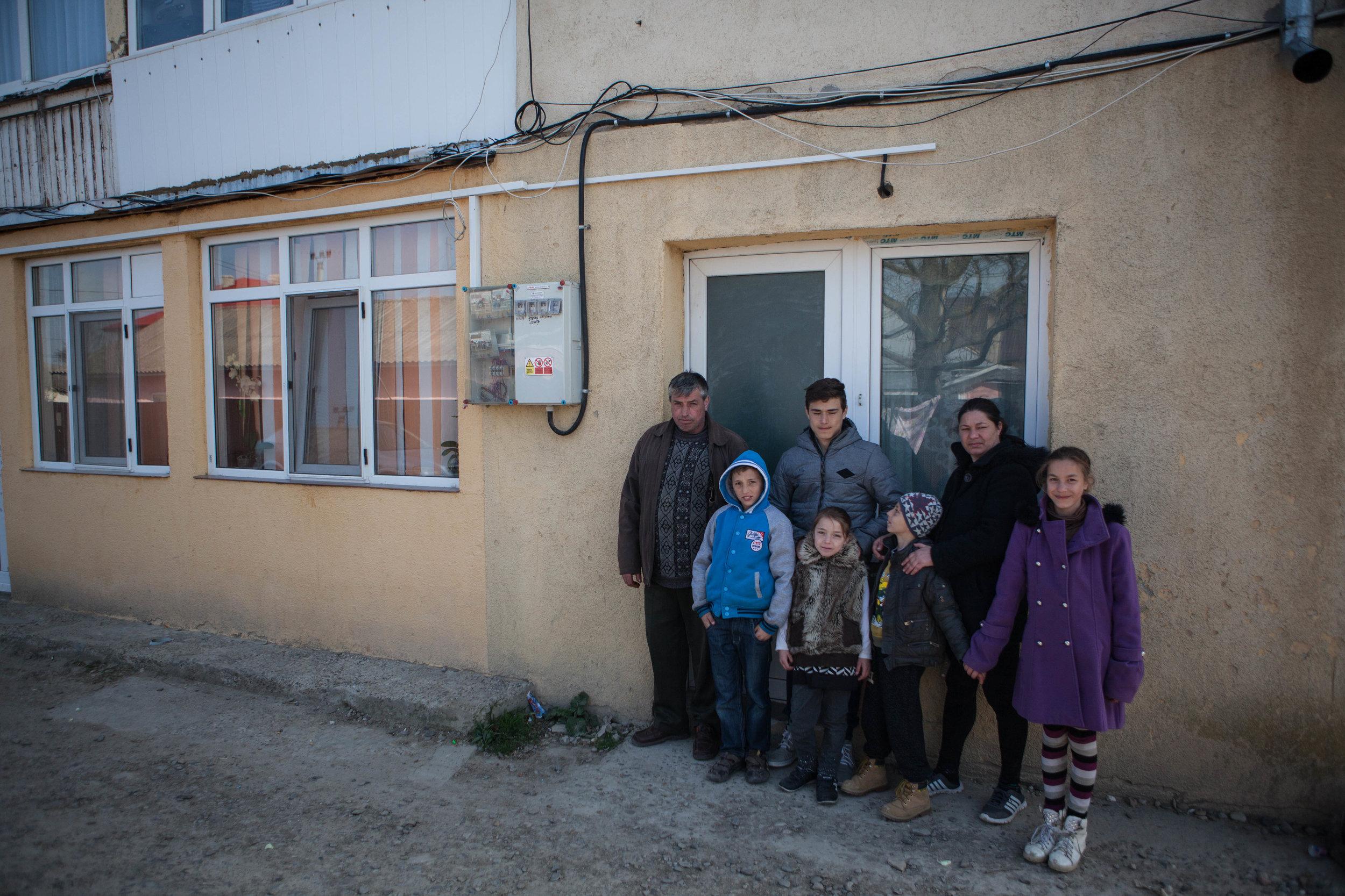 Familia Avram în fața vechii locuințe