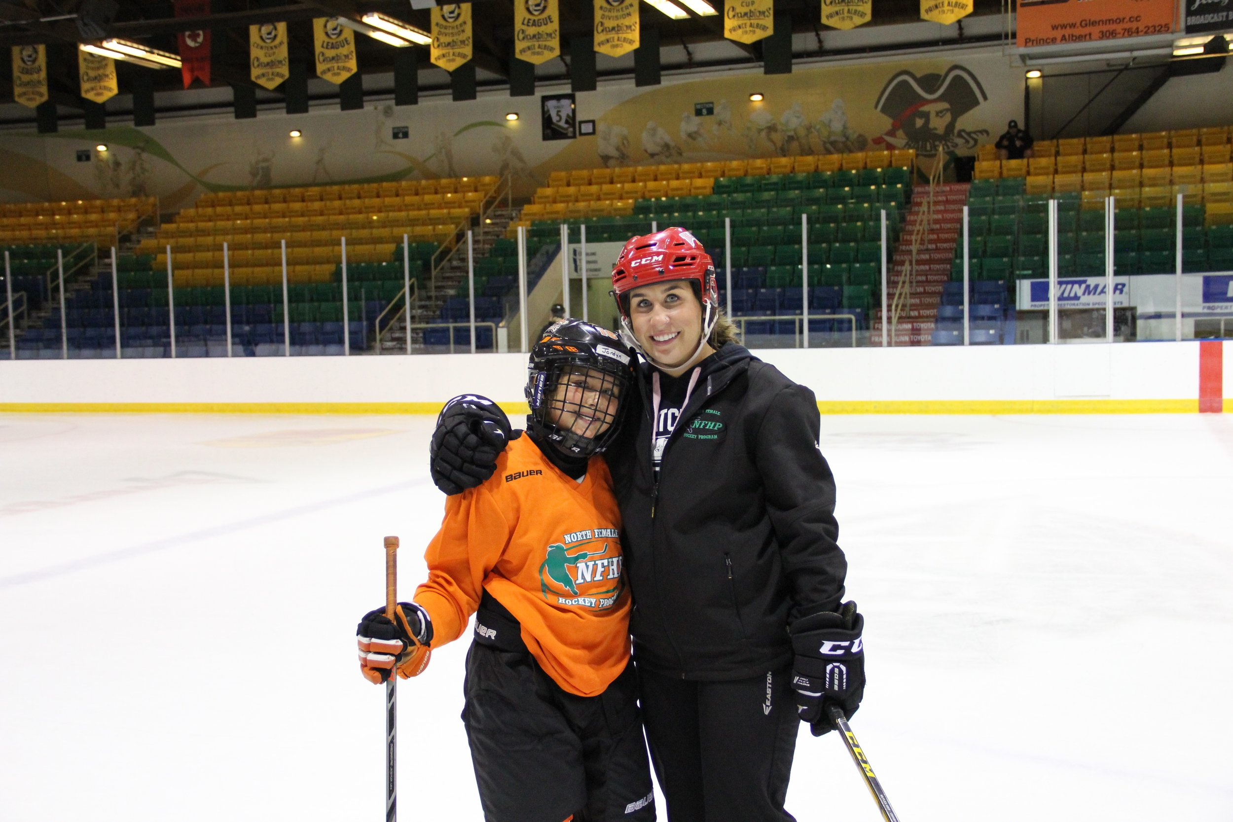 Coach & player posing on the ice.