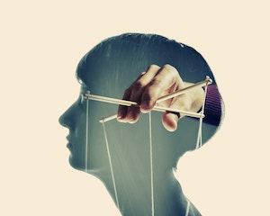 Silhouette of a woman's profile and within the woman's head is a man's hand holding marionette strings.