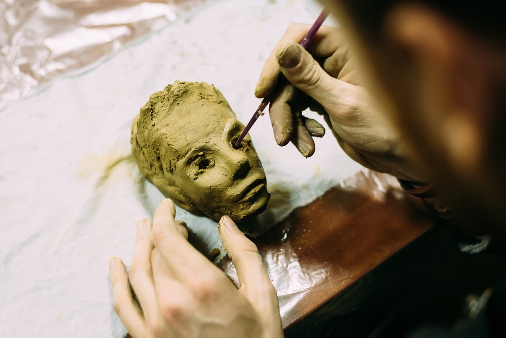 Person working with clay to create a person's head