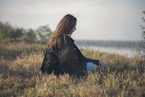 Woman with long brown hair sitting in a field