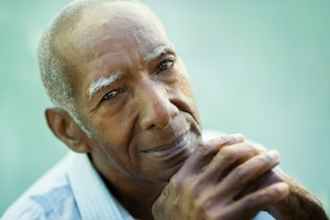 Closeup of an elderly African American man smiling serenely with his hands clasped under his chin.