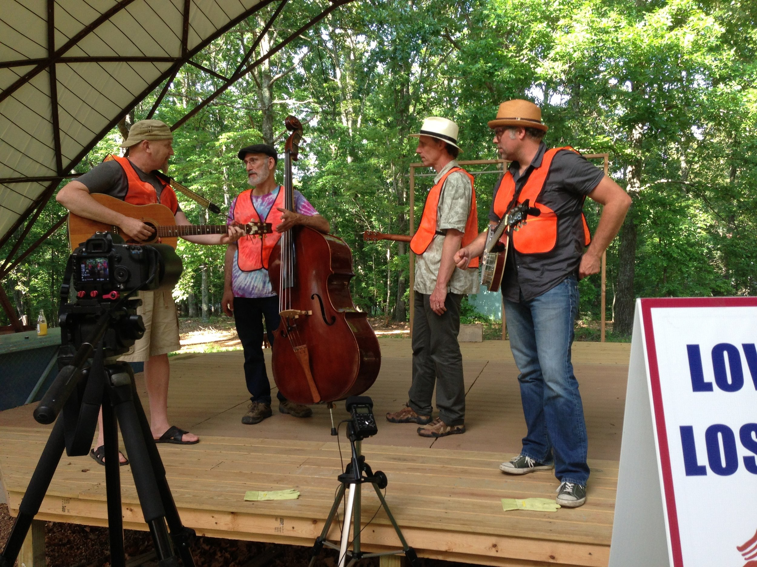 "Chuck McCarthy, Rick Diamond, Todd Elgin and Shawn Byrne work out the fine points of their original song ""Love the Land, Lose the Litter"" during its premiere (only) public performance on The Farm stage. Scroll to the top of this page for the lyrics."