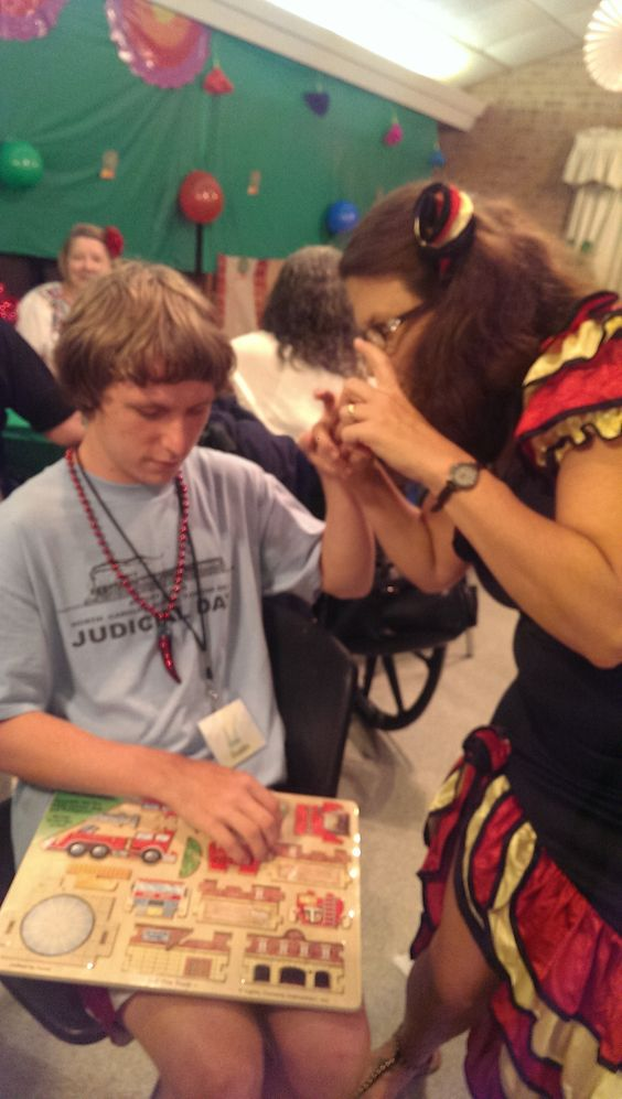 Image Description: SSP helping deaf-blind camper at Camp Dogwood 2014. The theme that year was Mexico. Camper has a puzzle and SSP is explaining the pieces.