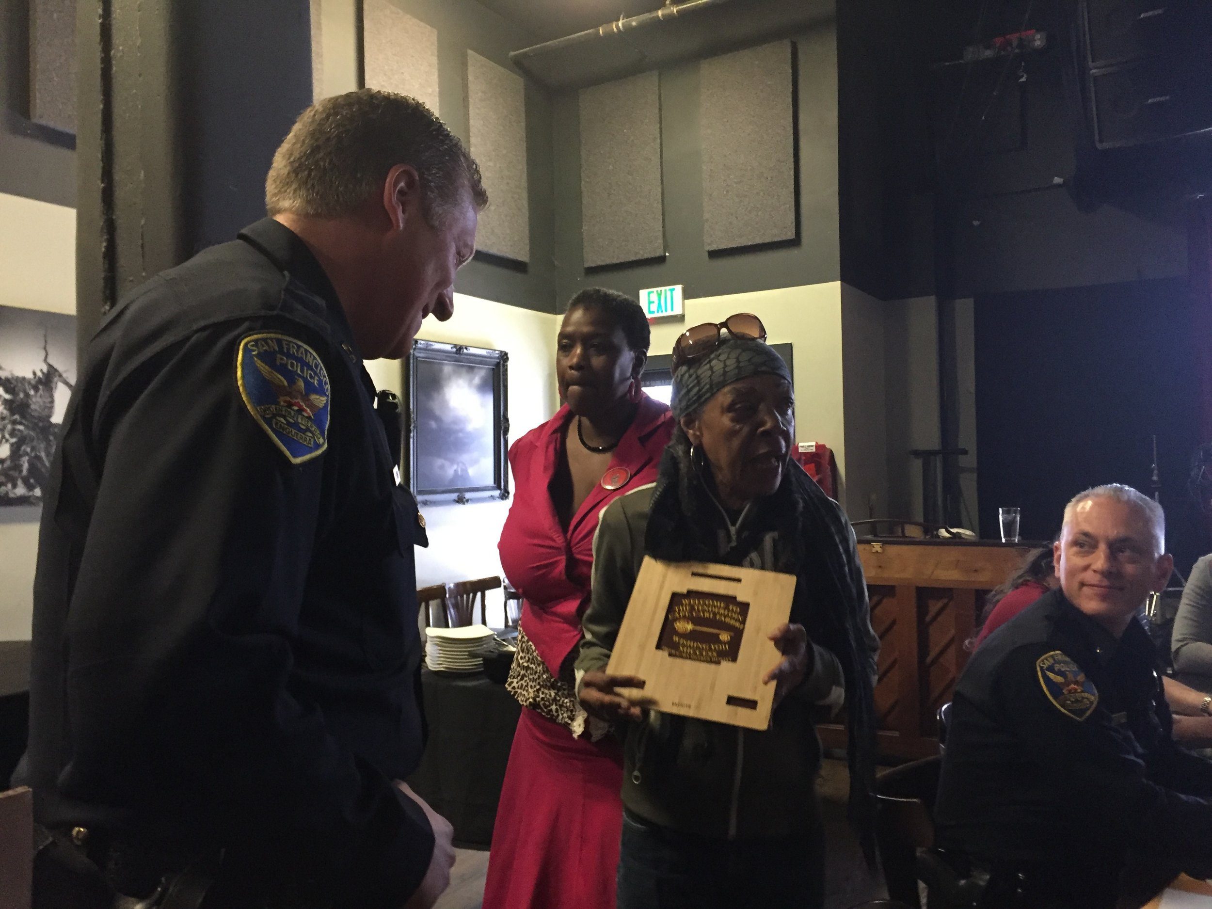 At a communtiy she coorganized with PianoFight,G-Ma presented the newly appointed TL Captain Carl Fabbri with a homemade, up cycled gift which she compared to the beauty and resiliency of the Tenderloin community. Also photographed, two of G-Ma's close friends, Debra, and Commander David Lazar.
