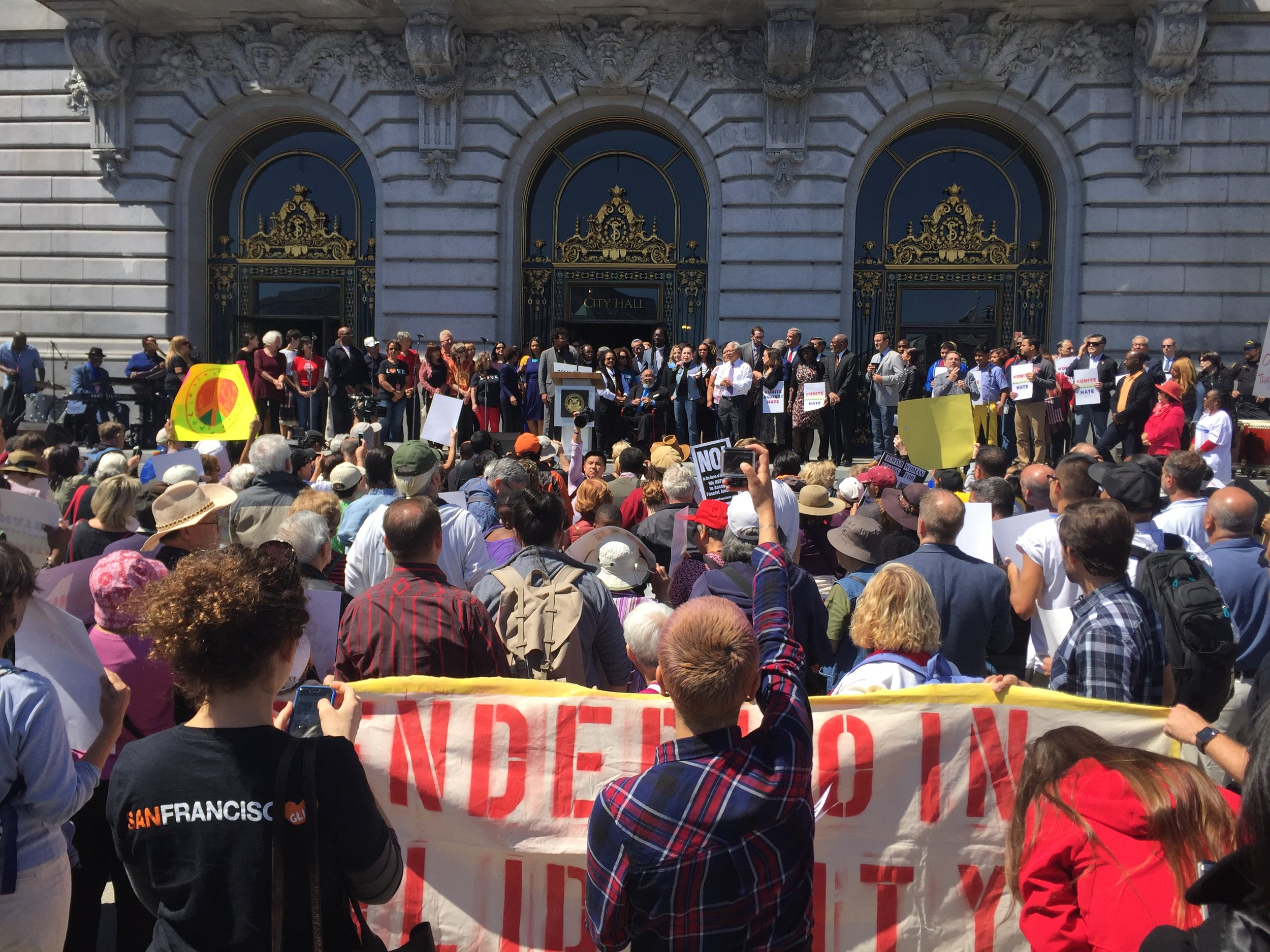 Photo: GLIDE clergy and leadership including founders Cecil Williams and Janice Mirikatani rally on the steps of City Hall with late Mayor Ed Lee to show support for immigrants amongst threats to sanctuary cities from Trump administration.