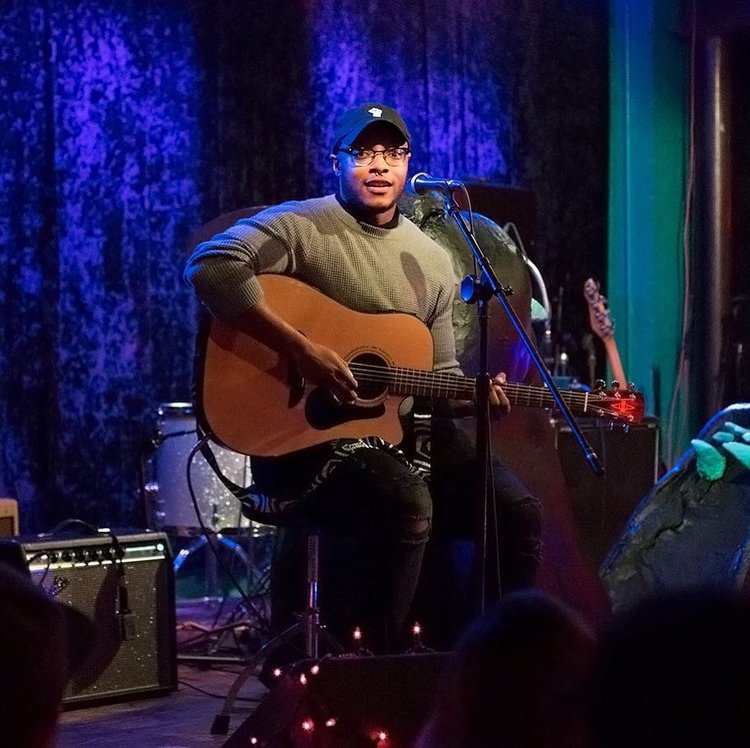 Elia Tamplin  {they/them/he/him}  singing, songwriting   Elia enjoys silence, food, dismantling systems of oppression, and creating lists and songs. Their strength is listening to and about other's experiences of life as they know it. 97% of their songs result from the collision of idealism, romantic comedies, Black folk ways of being, listening to other people's experiences, tensions with religion, and a perpetual state of melancholy and existential crisis.   Instagram