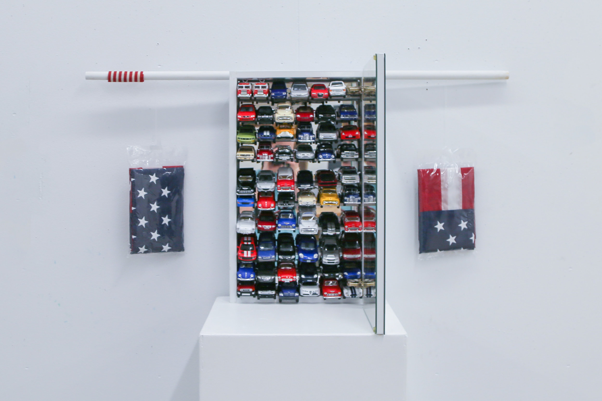 Untitled, 2018  ( Toys  Series): die cast toy cars, medicine cabinet, wood, flag