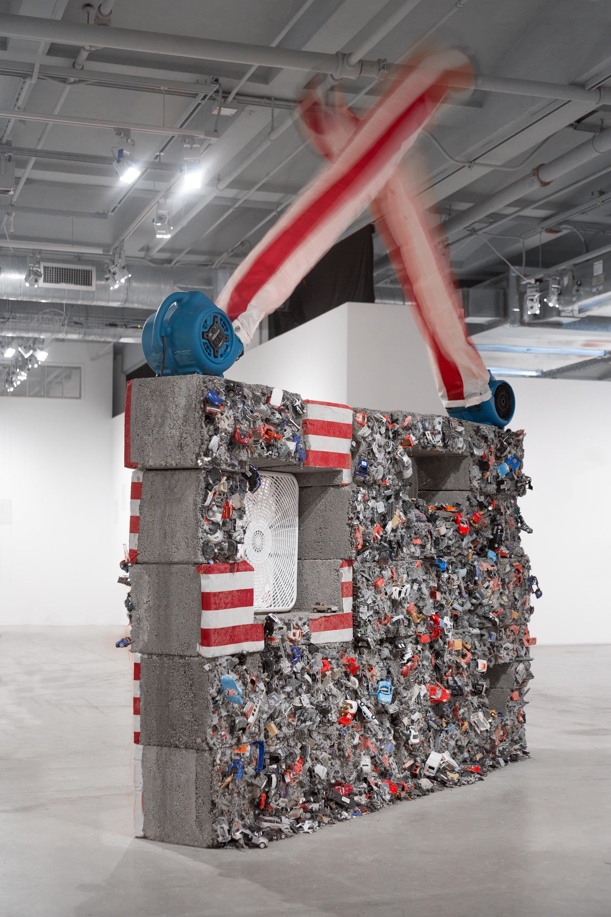 Detroit, 2019  concrete, toy cars, fans, U.S. flags (back view)