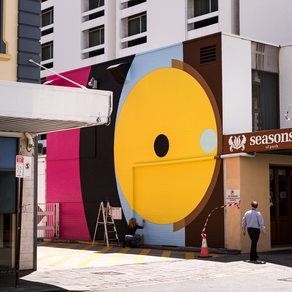 Historic Heart Mural Artwork 1 (2017) - Artist Helen SmithPier Street, PerthA non-referential geometric abstraction, Helen often explores bold conjunctions of colour and shape to enliven surfaces. The brilliant use of hot pink, brown, yellow and acqua in circular motifs creates a bold interplay with the square web of Jeremy Kirwan-Ward's work on the opposing walls on Pier Street.For further details on the artist visit Helen Smith's website